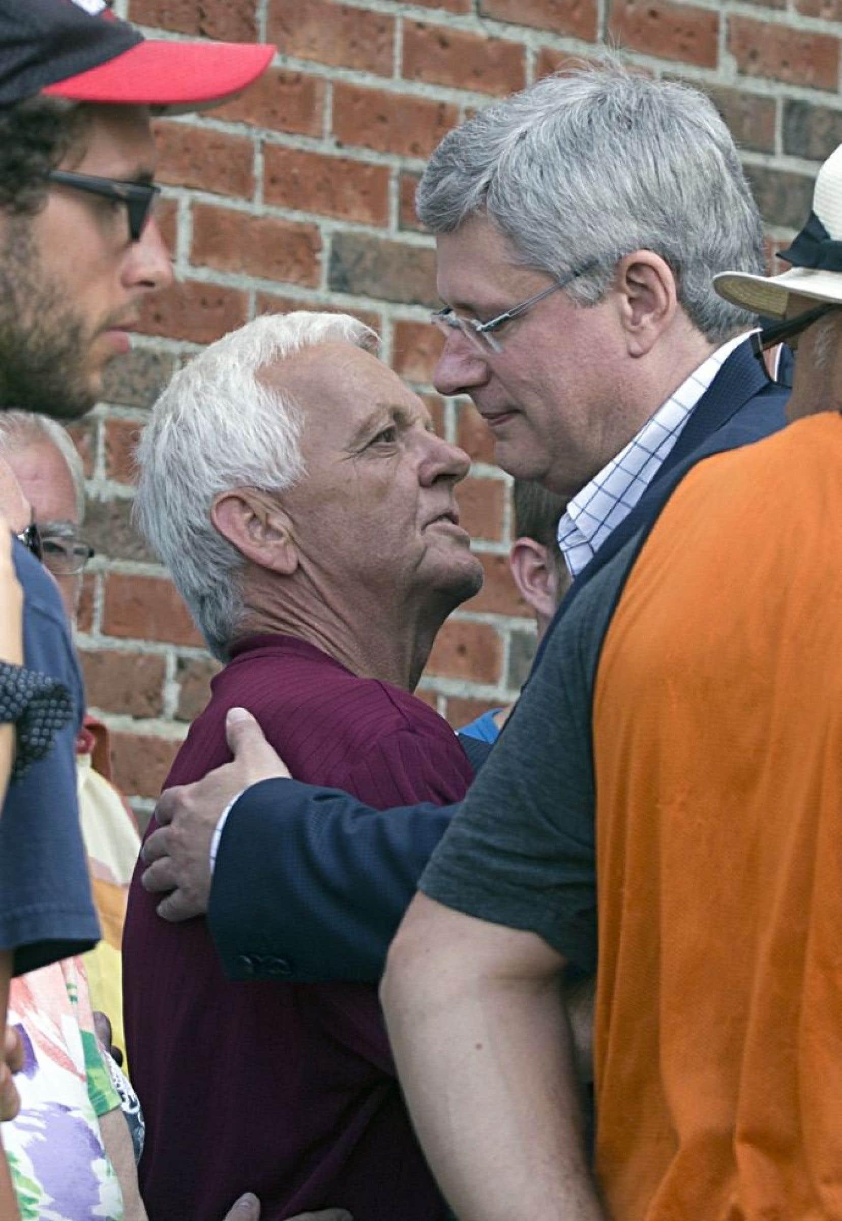 Le premier ministre canadien Stephen Harper, qui a comparé le lieu de l'accident à une «zone de guerre», sympathise avec un sinistré.