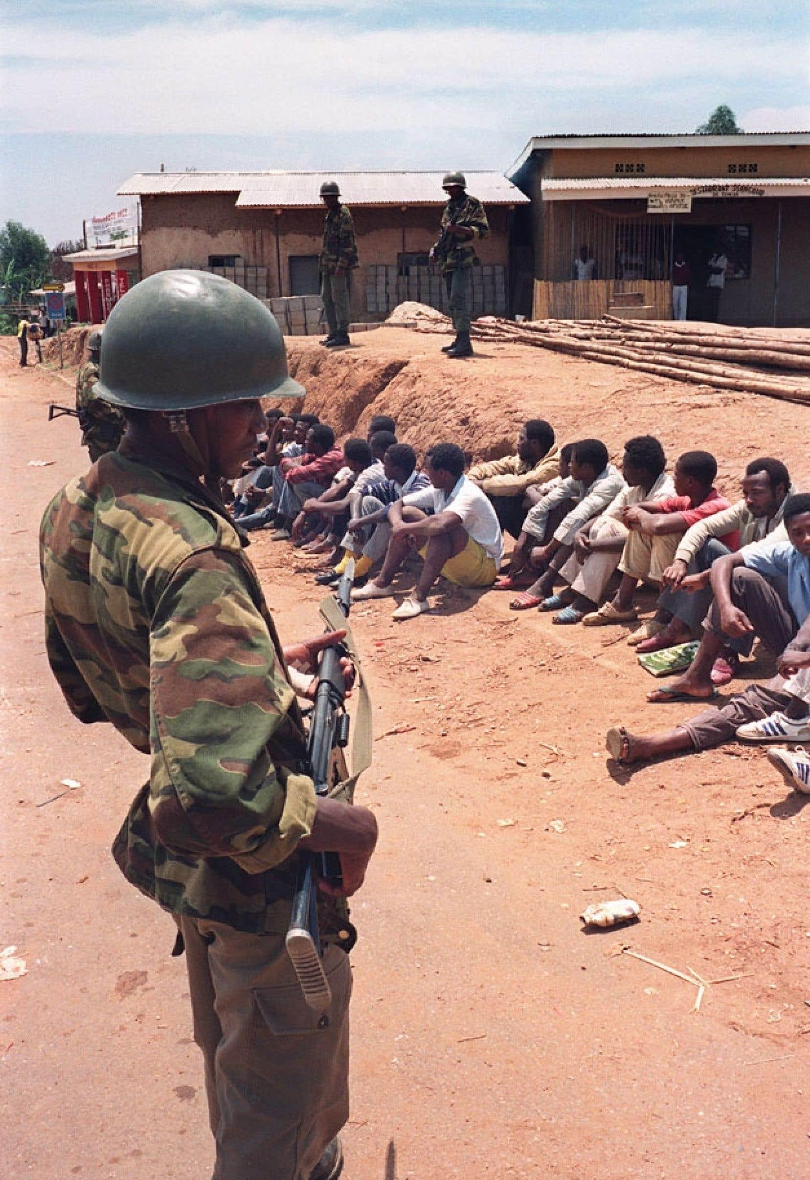 Un soldat surveille des civils arrêtés après l'invasion des hommes du Front patriotique rwandais, en 1990. Les affrontements ont alors débuté avec les forces gouvernementales.