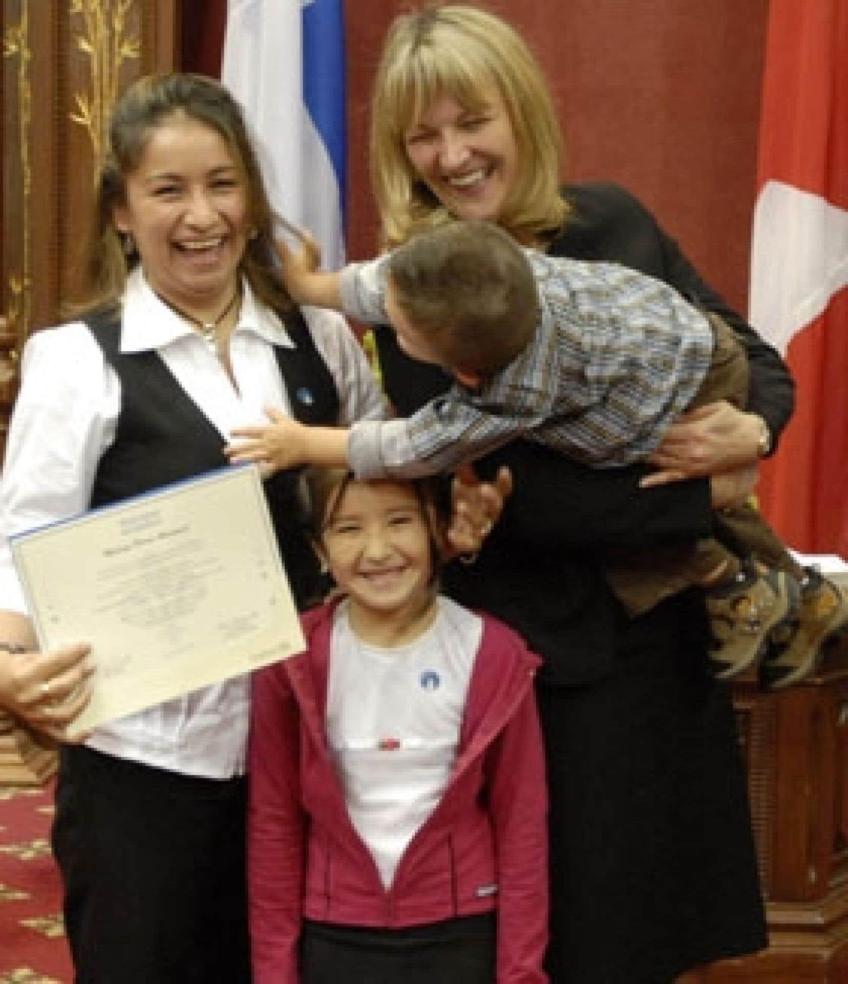La ministre de l'Immigration Lise Thériault (au centre tenant un enfant qui souhaite visiblement retrouver sa mère) souhaite la bienvenue à l'épouse et aux enfants de Daniel Augusto Nunez Acosta, un Québécois d'origine colombienne établi au