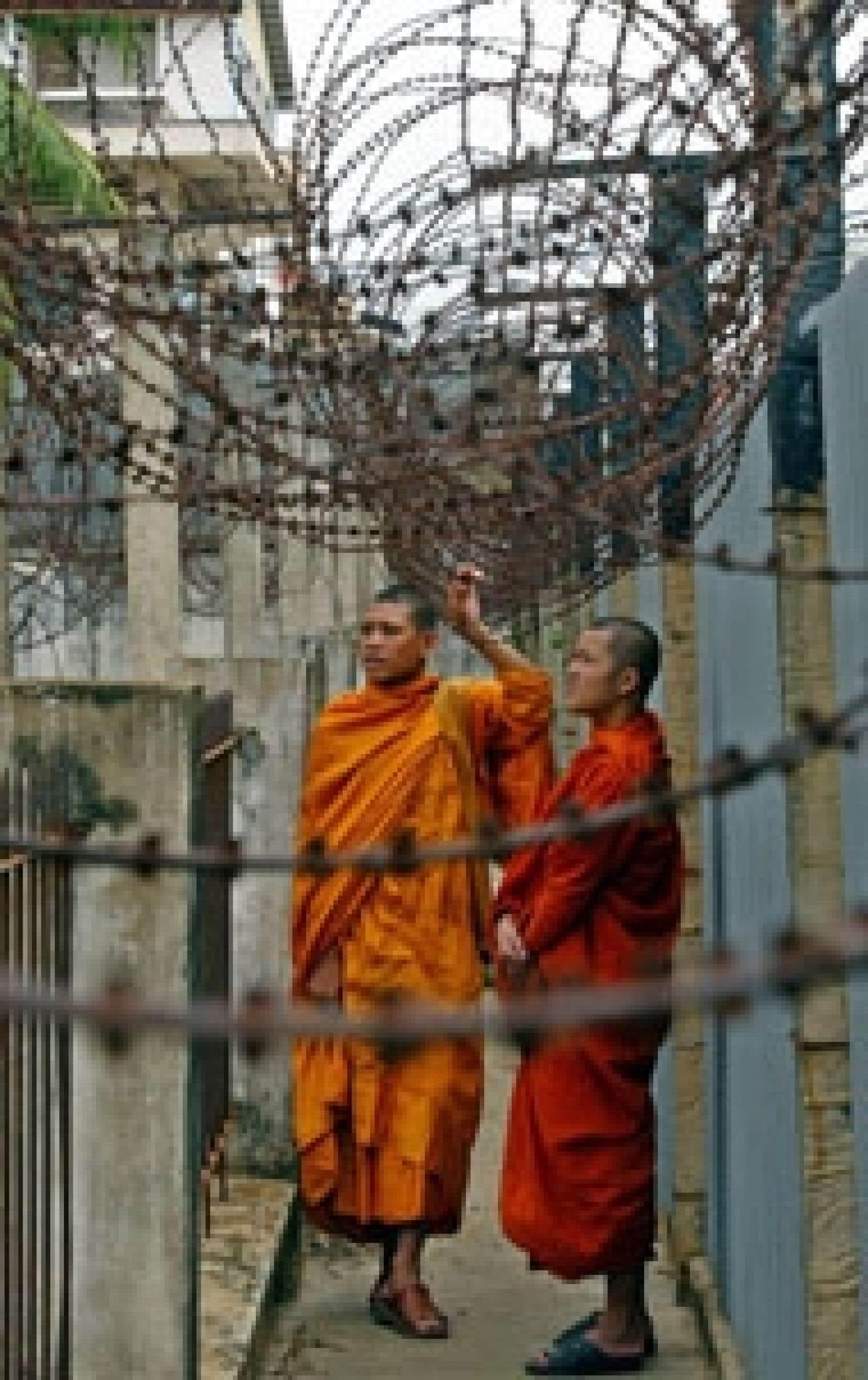Des moines bouddhistes examinent les barbelés de la prison khmère rouge S-21 reconvertie depuis en musée commémorant le génocide commis sous le régime de Pol Pot dans les années 1970.
