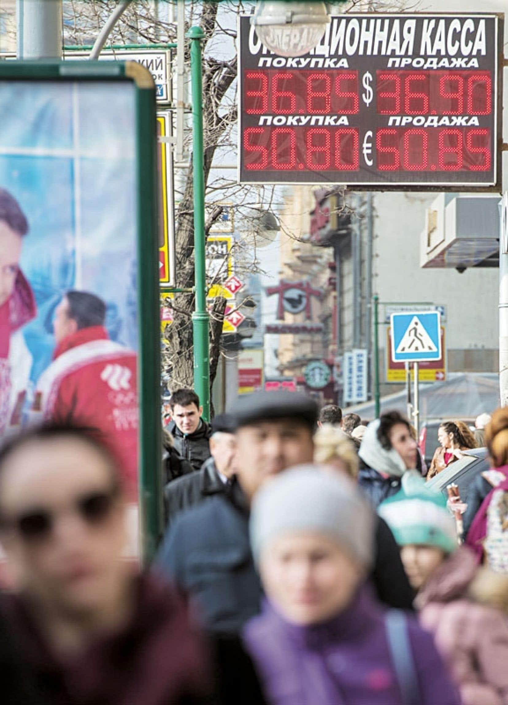 Des Moscovites marchent sous un panneau indiquant la valeur du rouble par rapport au dollar et à l'euro.