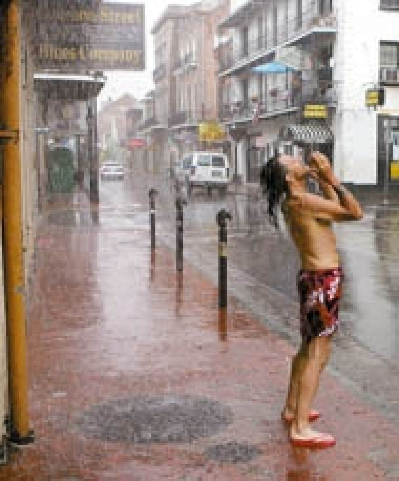 L'ouragan Rita s'approche des côtes américaines, qu'il doit frapper la nuit prochaine. Des vents forts et une pluie abondante ont balayé La Nouvelle-Orléans hier, permettant à ce commerçant de Bourbon Street, dans le quartier français, de pr