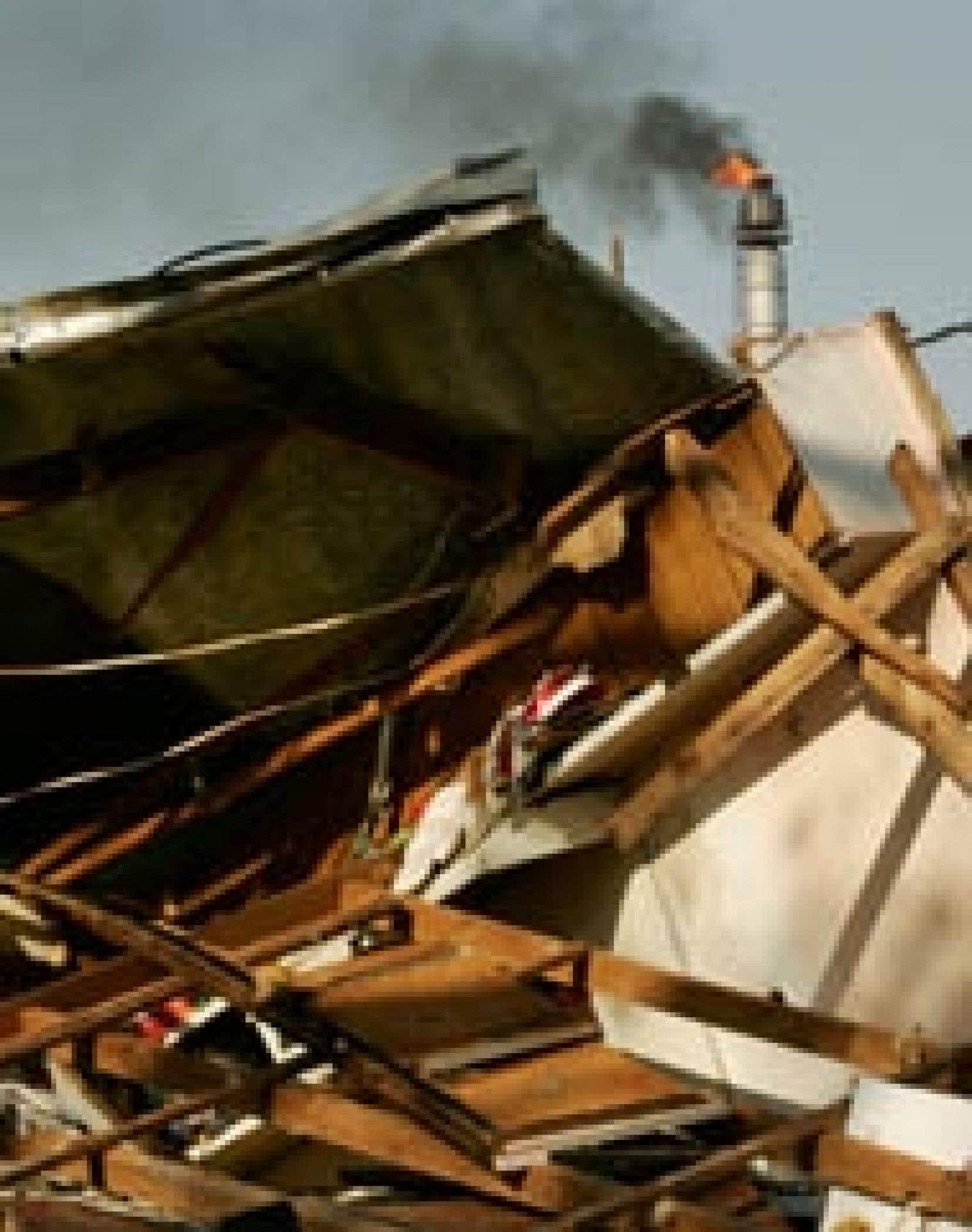 La flamme d'une raffinerie s'élève derrière les débris de maisons en Louisiane. Il est très difficile de prévoir l'évolution des cours du pétrole dans le contexte actuel en raison de l'évaluation toujours incomplète des dommages causés