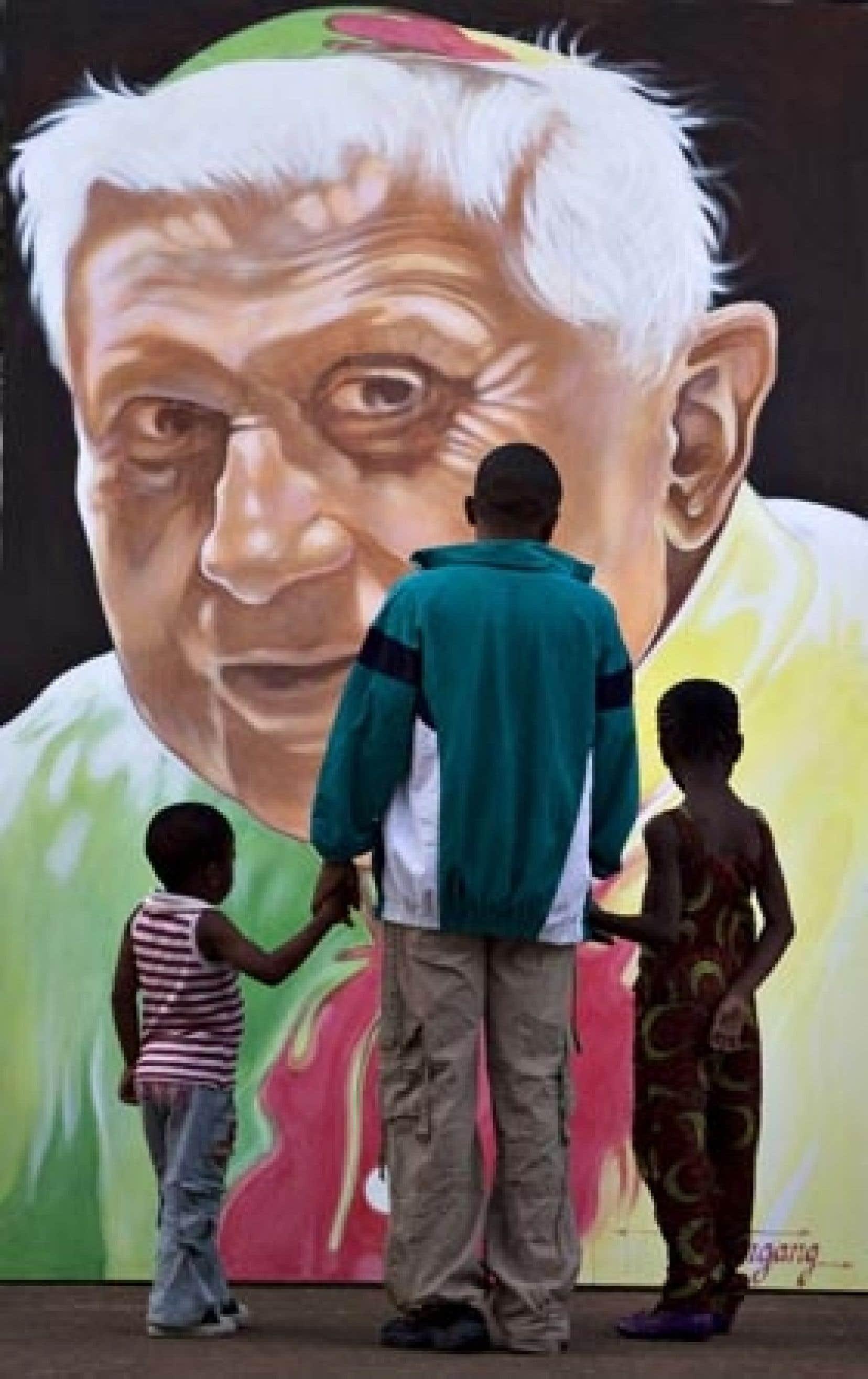 Une famille regarde un portrait du pape Benoît XVI, peint aux couleurs du Cameroun, à l'extérieur de la basilique Marie Reine des apôtres, à Yaoundé, où il célébrera la messe mercredi.