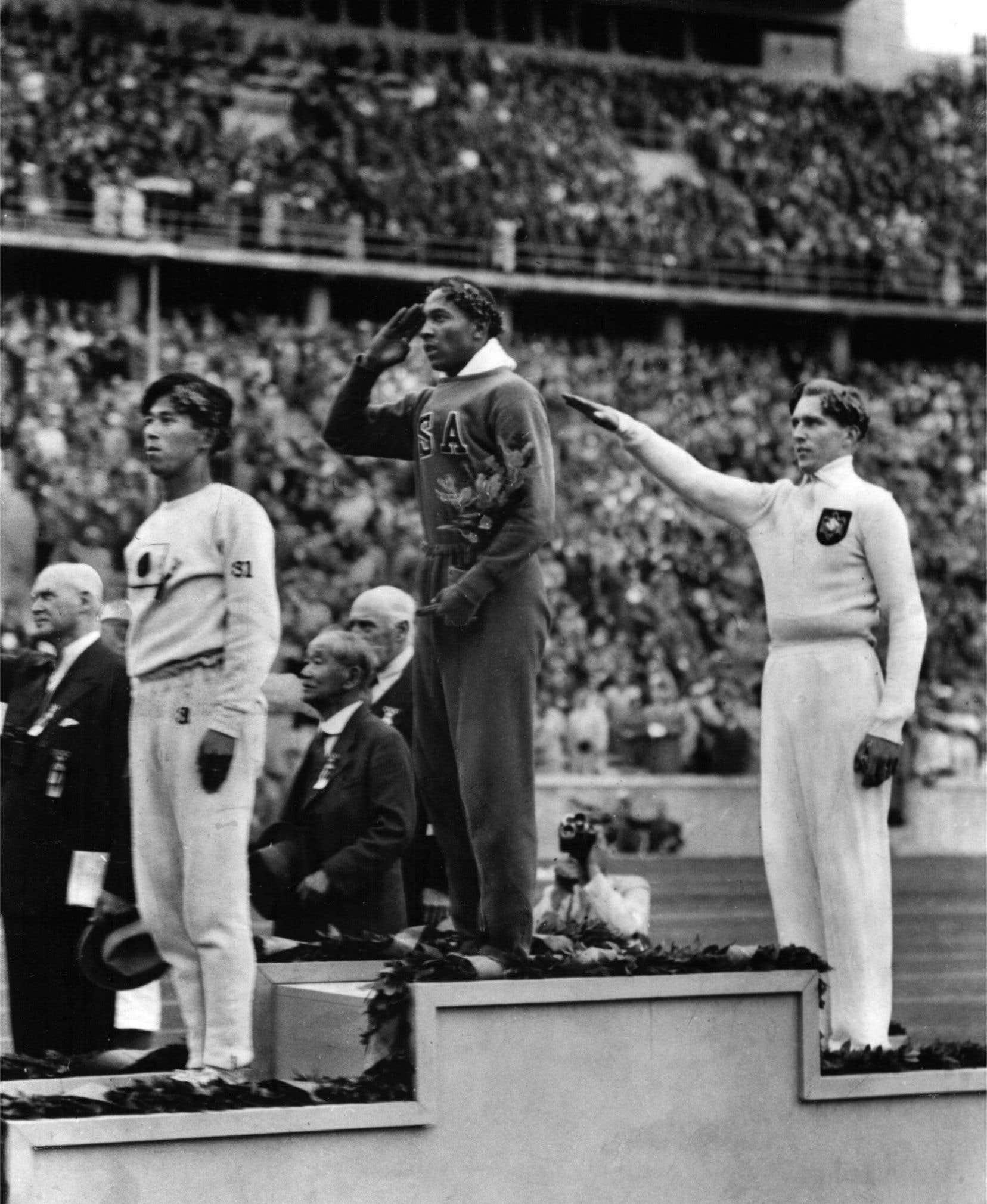 Jesse Owens monte sur la plus haute marche du podium après sa victoire au saut en longueur.