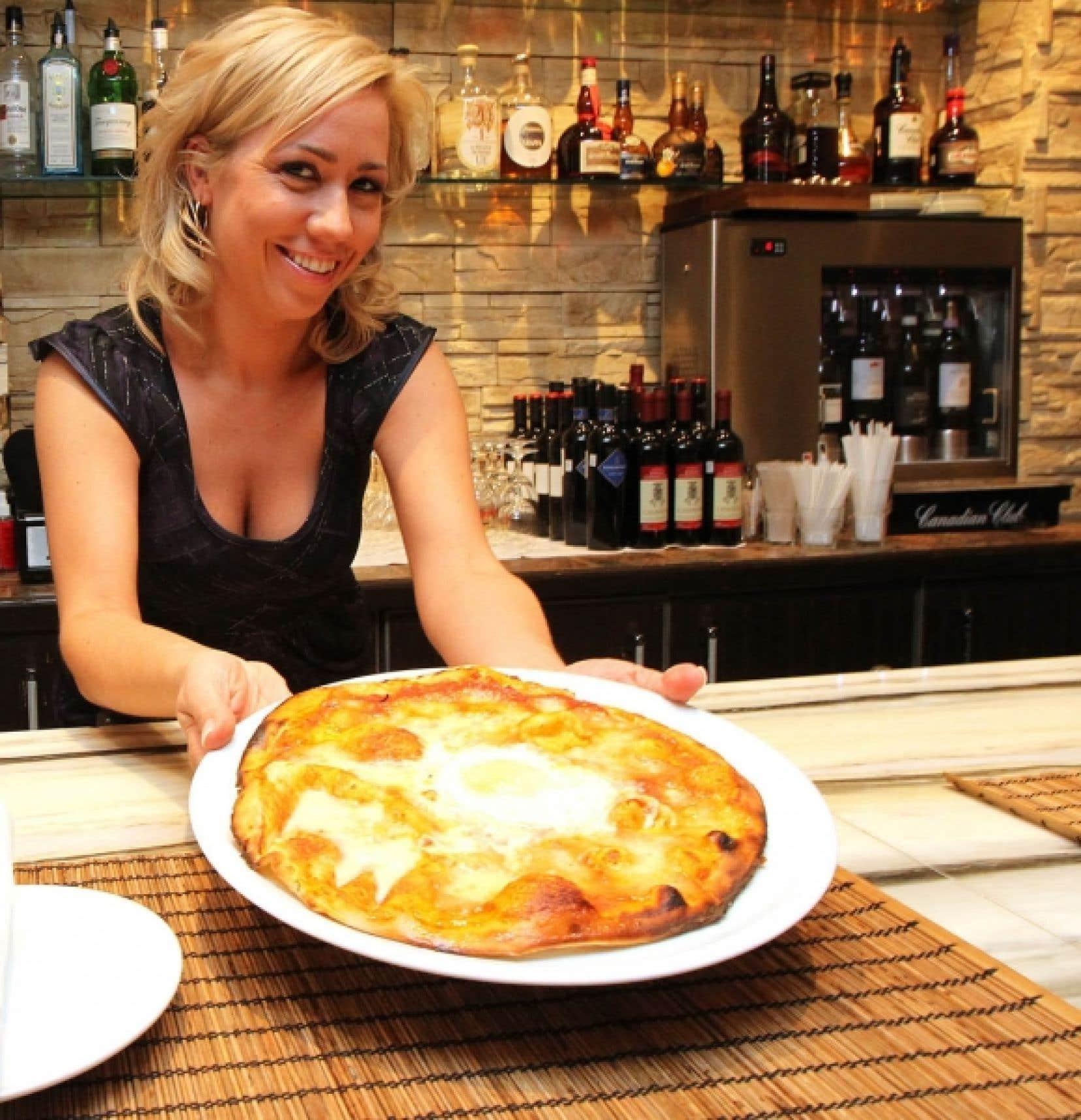 La copropriétaire de l'Arlequino, Marie-Ève Lalancette, sert la classique Cosenza, une pizza à pâte fine garnie d'une bonne sauce tomate, de fromage et d'un œuf encore mollet