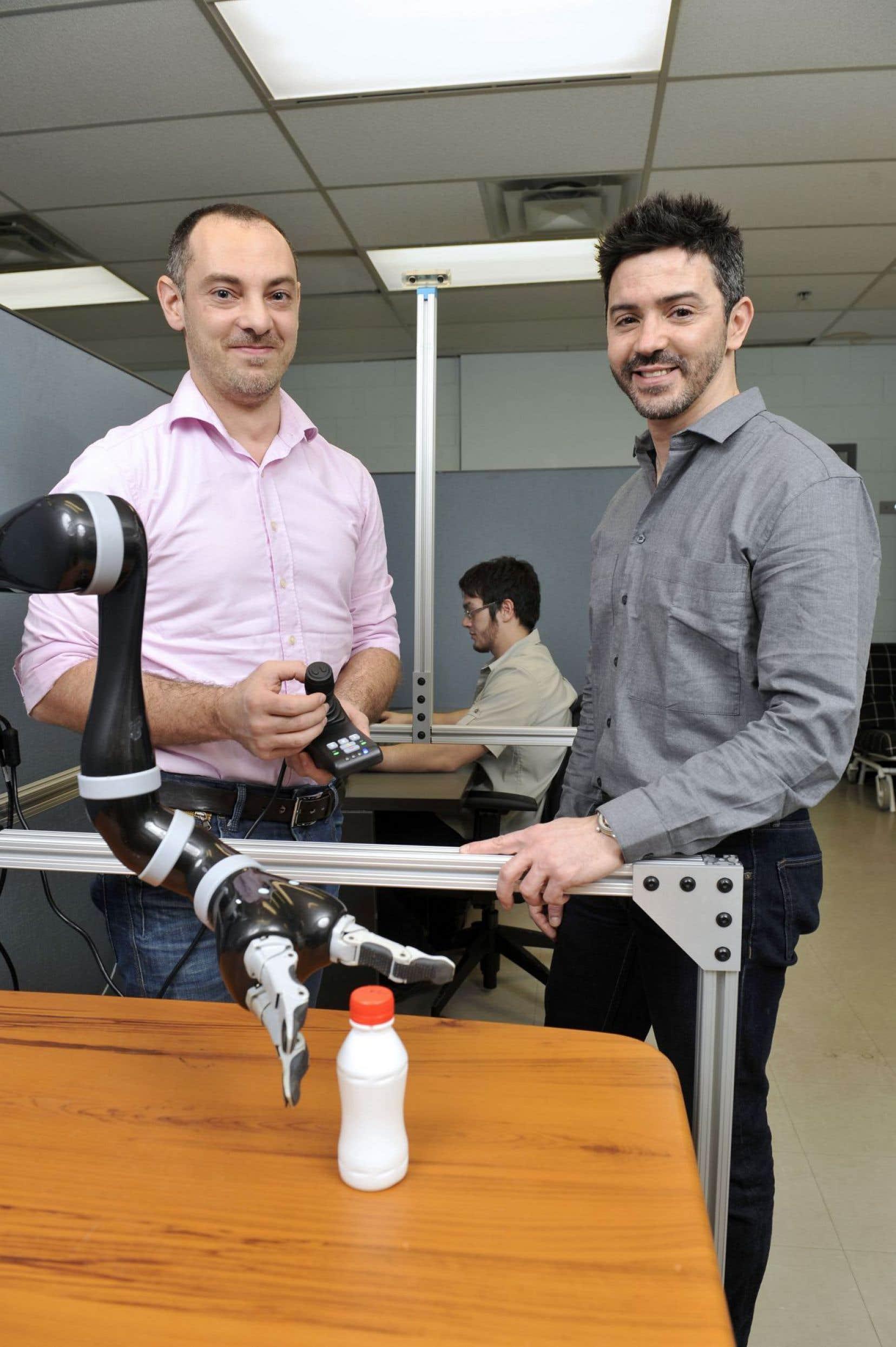 Le Pr Maxime Raison en compagnie de son collaborateur, le Pr Sofiane Achiche, derrière un bras robotique d'adaptation