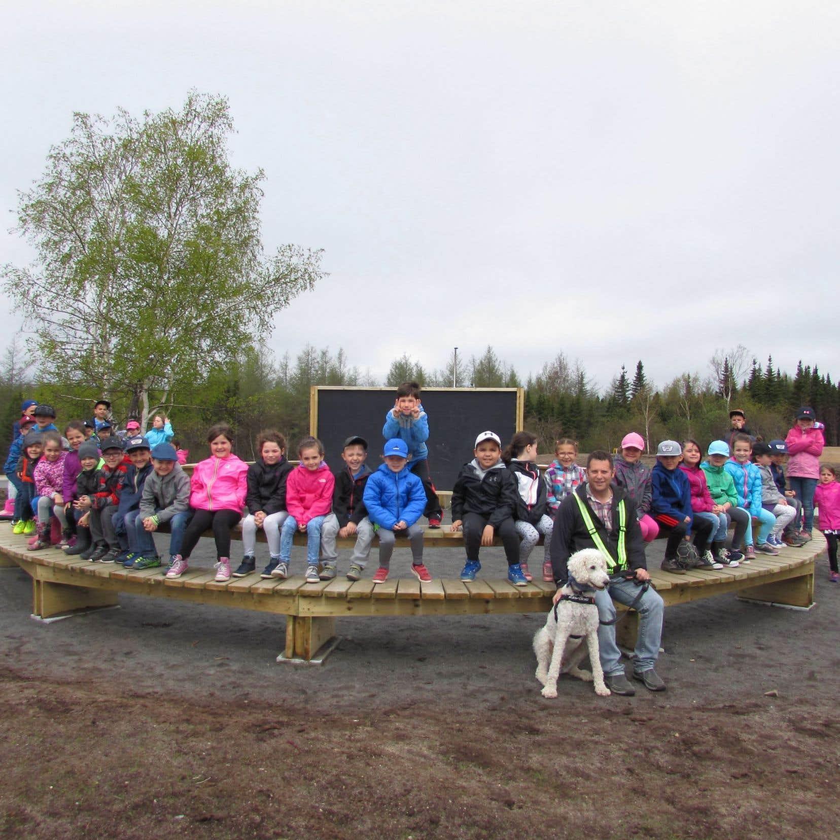 Les élèves de l'École du Boisé ont accès à une salle extérieure en bois circulaire au centre de laquelle est placé un tableau noir qui permet au professeur de donner son cours.