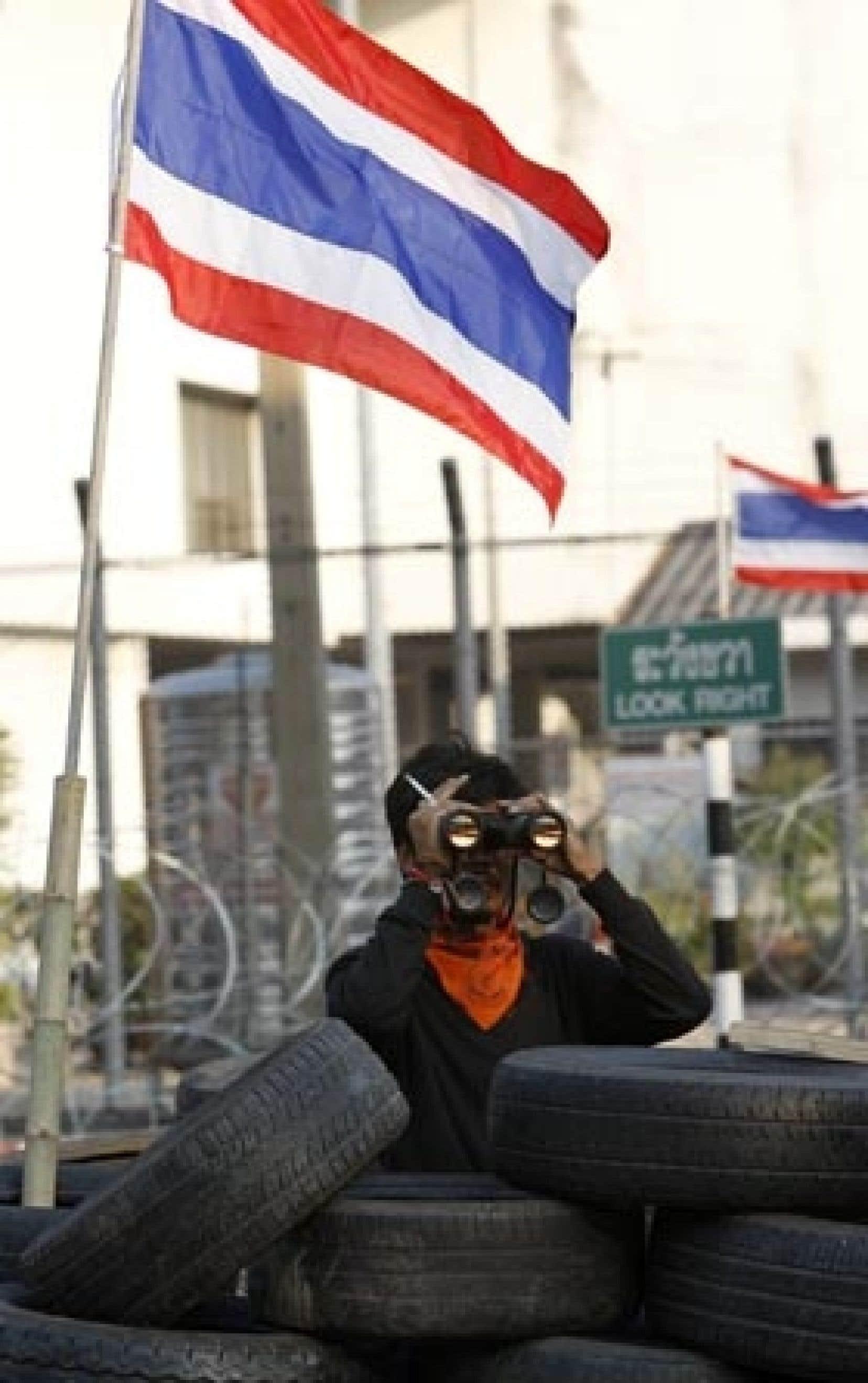 Un opposant surveillait les mouvements des policiers hier à l'aéroport de Bangkok.