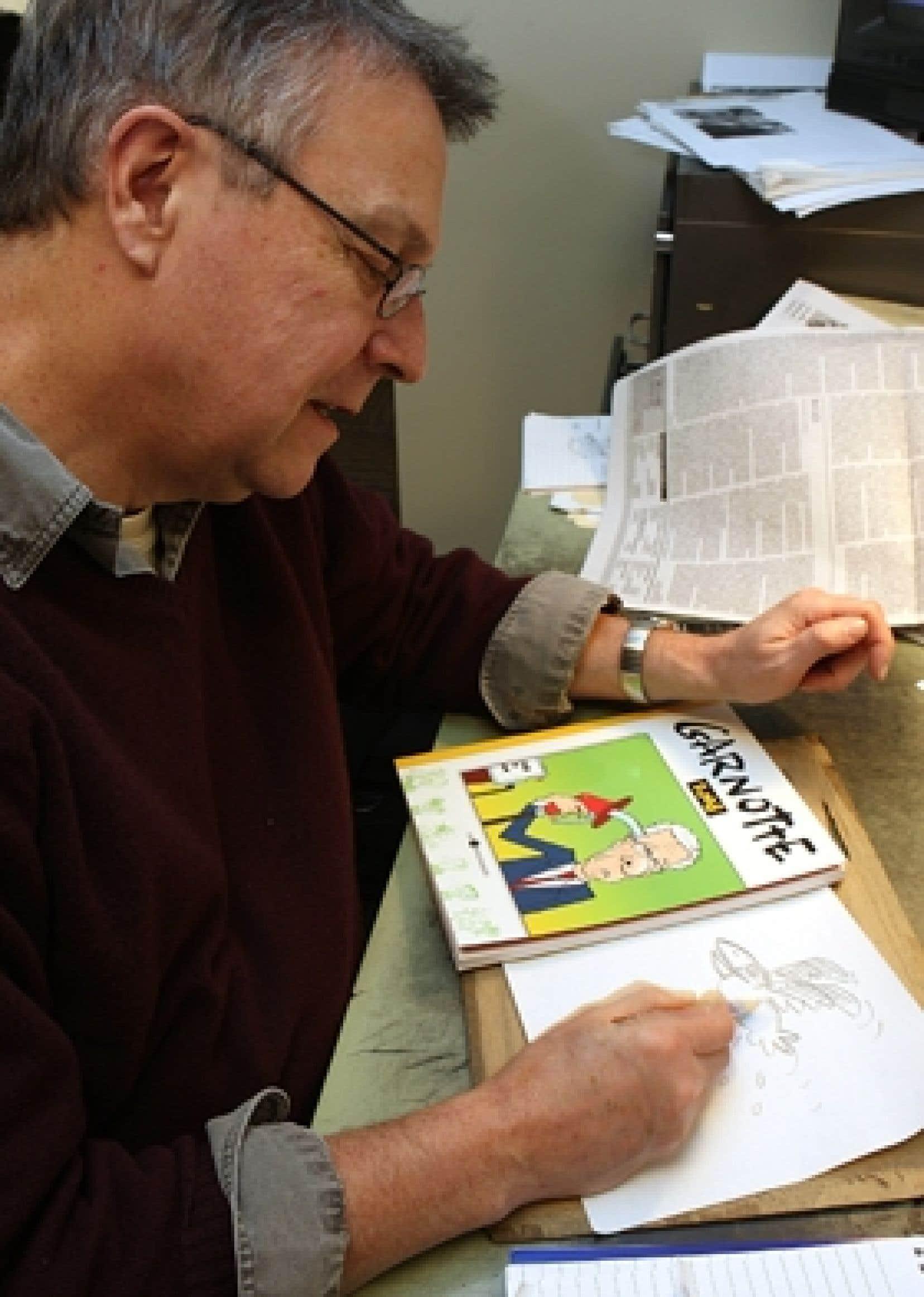 Michel Garneau, dit «Garnotte», à sa table à dessin, au Devoir