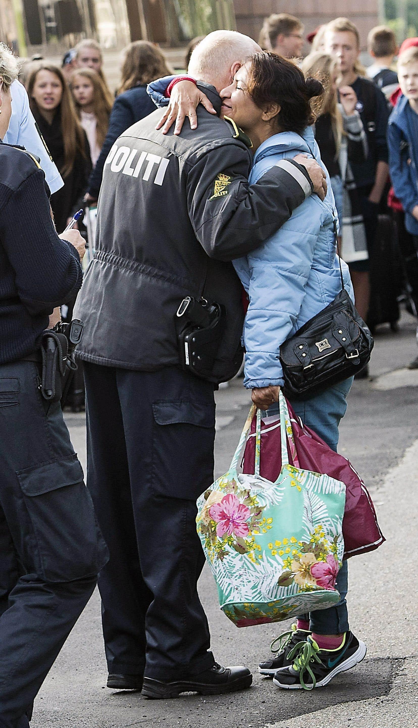 Émue d'être parvenue à la fin de son périple, une demandeuse d'asile arrivée d'Irak ou de Syrie a enlacé un policier danois à sa descente du train, à Copenhague, en septembre 2015.