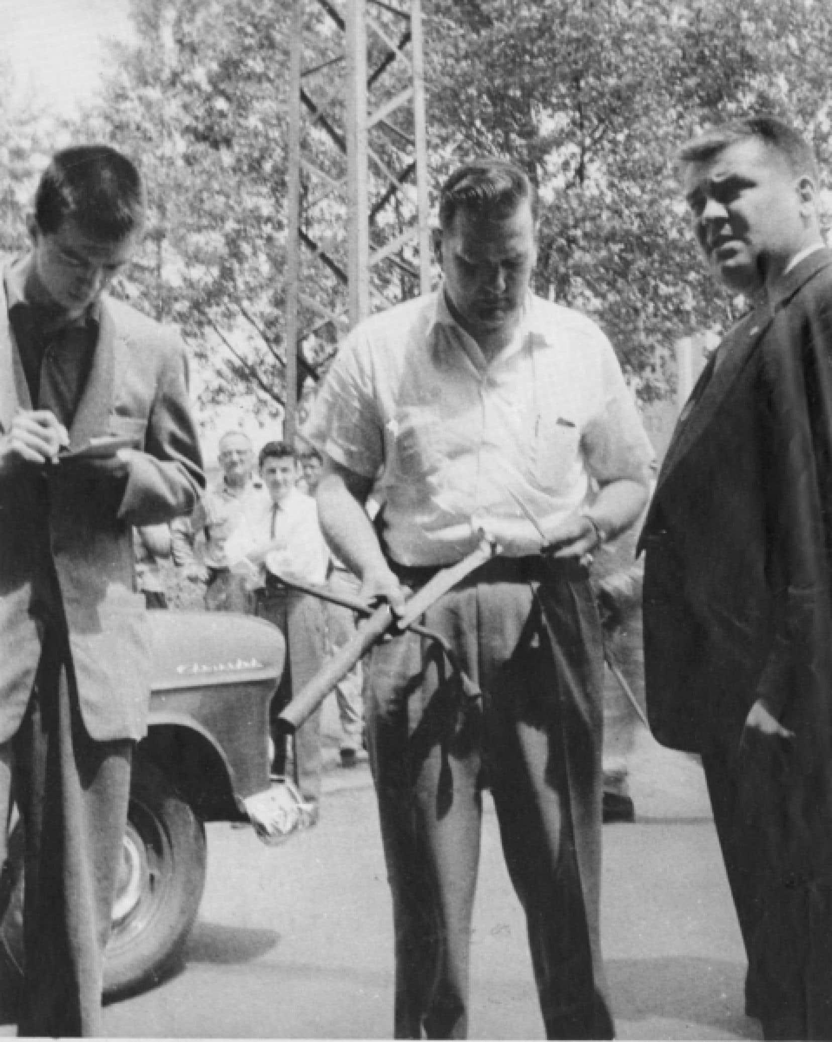 Le journaliste Guy Lamarche (&agrave; gauche), accompagn&eacute; de deux policiers en civil, pendant sa couverture de la campagne &eacute;lectorale provinciale de 1956.<br />