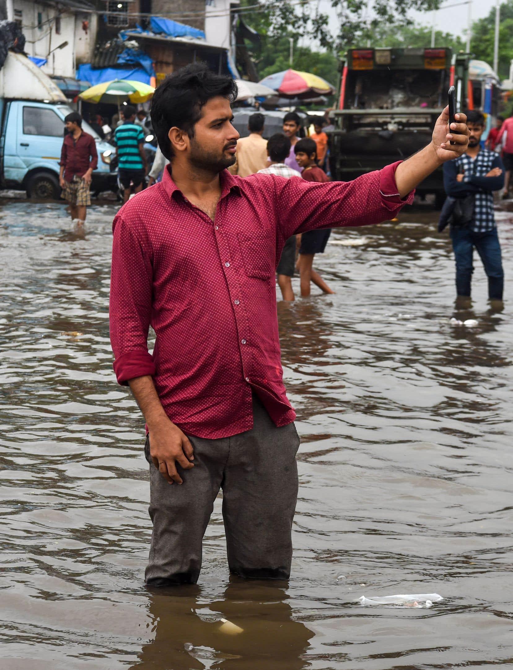 Un homme croque un égoportrait alors que les pluies de la mousson inondent les rues de Mumbai, en août dernier.