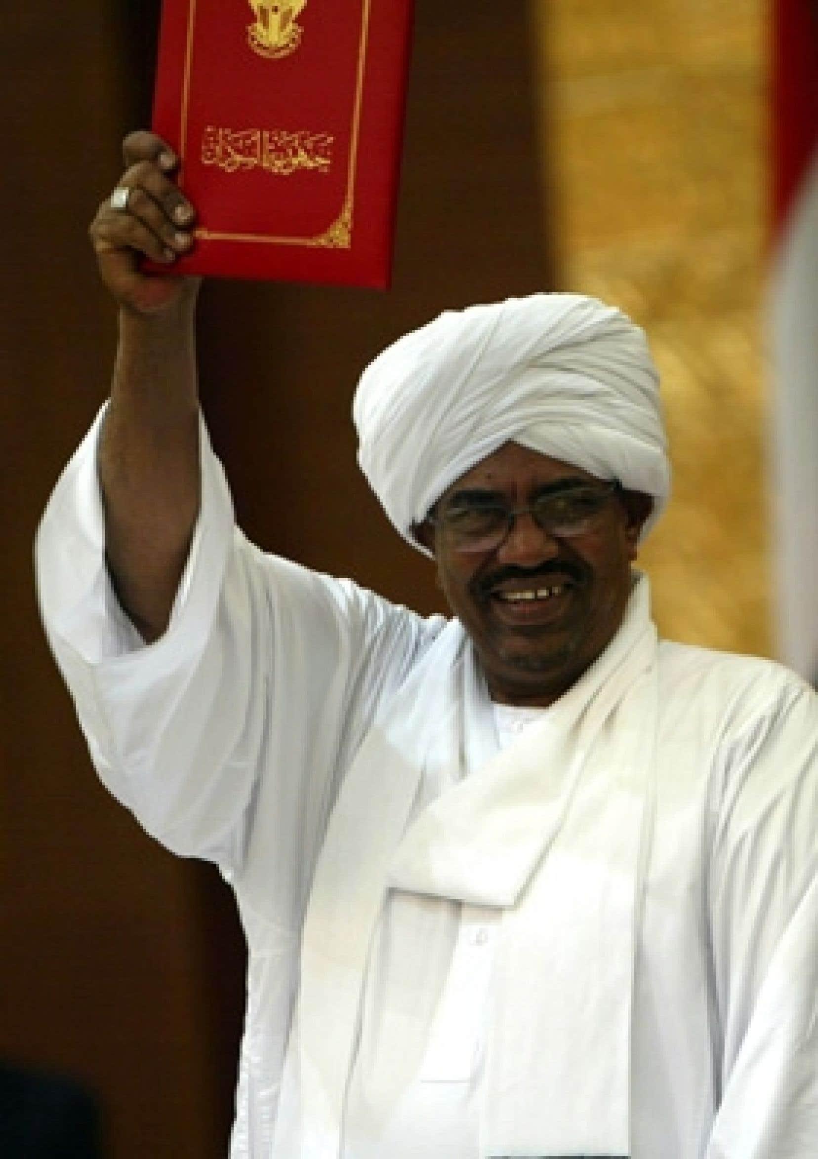Le président soudanais Omar el-Béchir brandit la nouvelle loi électorale signée hier. Un mandat d'arrêt a été requis contre lui à la suite d'accusations de génocide au Darfour.