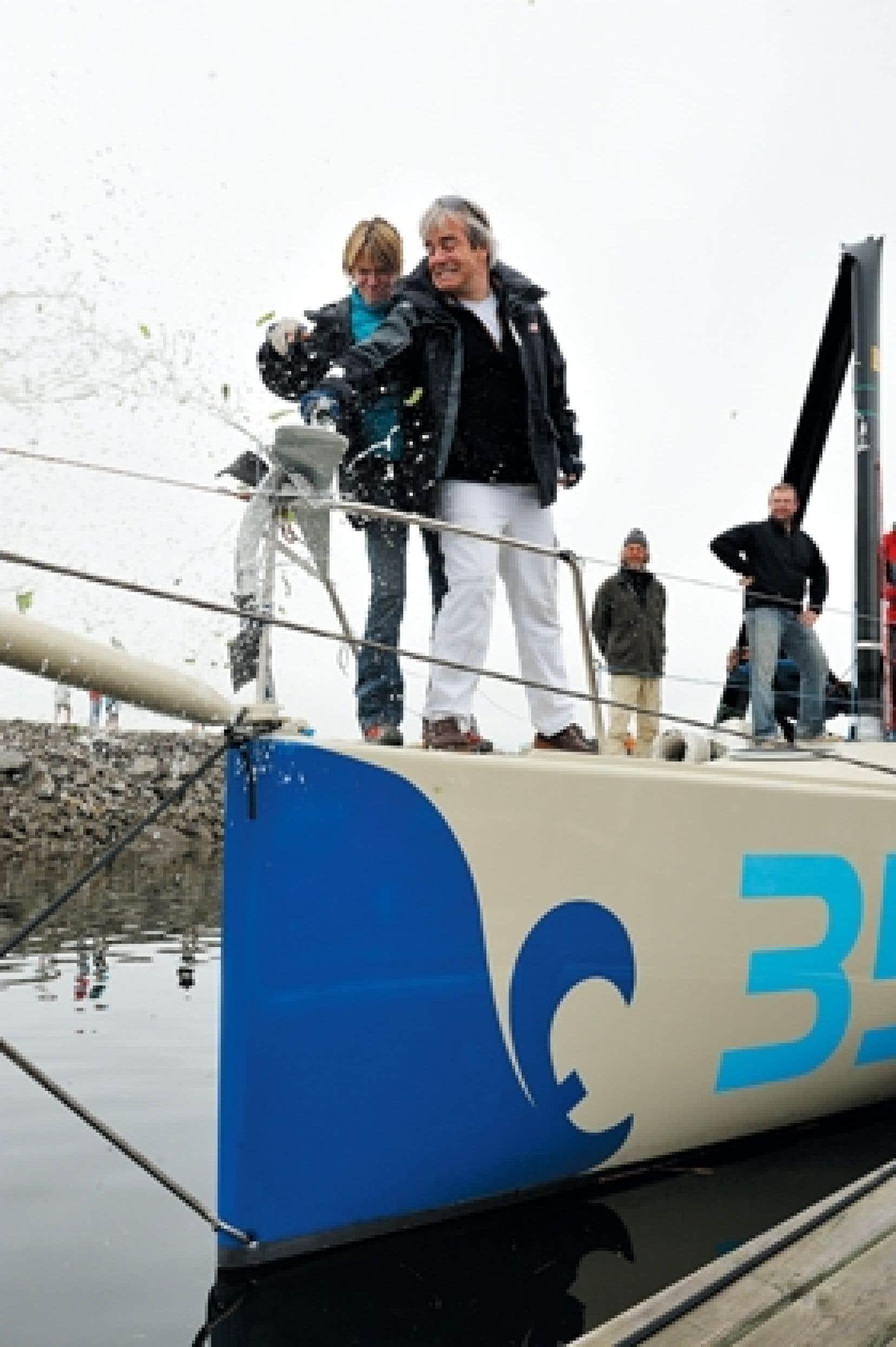 Joblo et Jean Lemire, marraine et parrain du voilier Bleu, fracassent la traditionnelle bouteille de bulles offertes à Neptune durant le baptême à Gaspé.