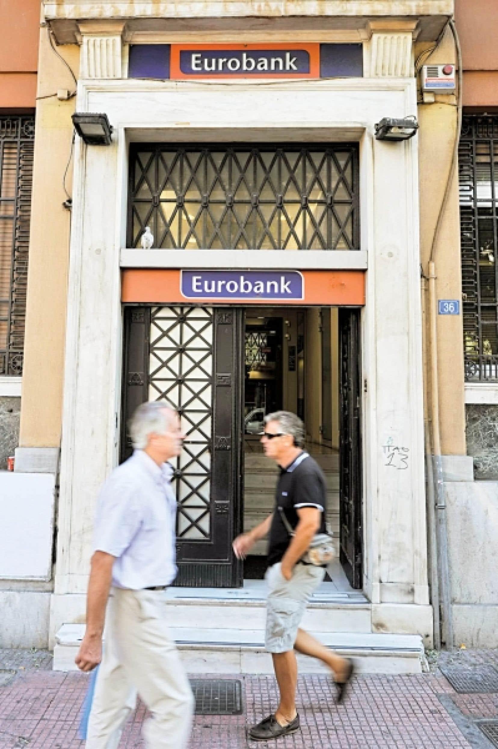 Des pi&eacute;tons passent devant une succursale ath&eacute;nienne de l&rsquo;Eurobank.<br />