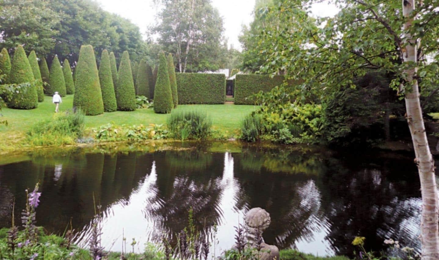 Les jardins de Quatre-Vents, dans Charlevoix, font partie des grands jardins privés de l'Amérique du Nord. Voici l'impeccable et impressionnante allée des thuyas et, à l'avant-plan, le lac des Libellules.