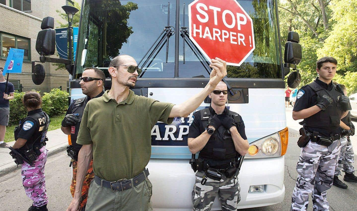 Des manifestants bloquent le bus de campagne de Stephen Harper lors de sa venue à Montréal le 2 août 2015.