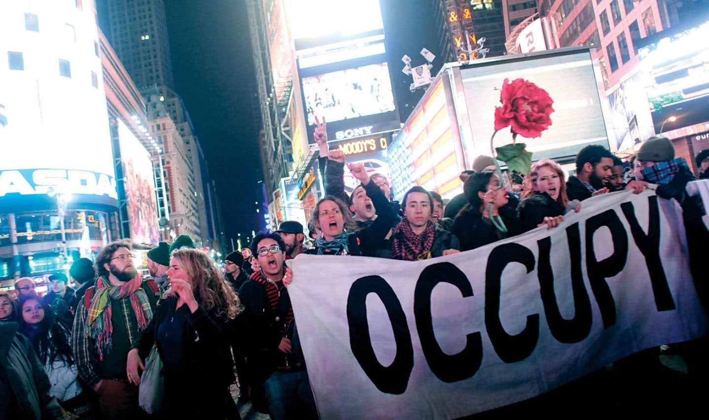 Des activistes d'Occupy Wall Street défilent à Times Square en décembre2011 pour souligner les trois mois du mouvement.