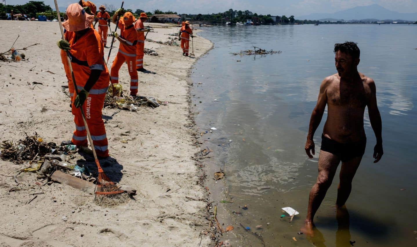 Des employés municipaux ramassaient des débris sur une plage de la baie de Guanabara, à Rio de Janeiro, en décembre 2015, où se tiendront les compétitions aquatiques aux prochains Jeux olympiques.