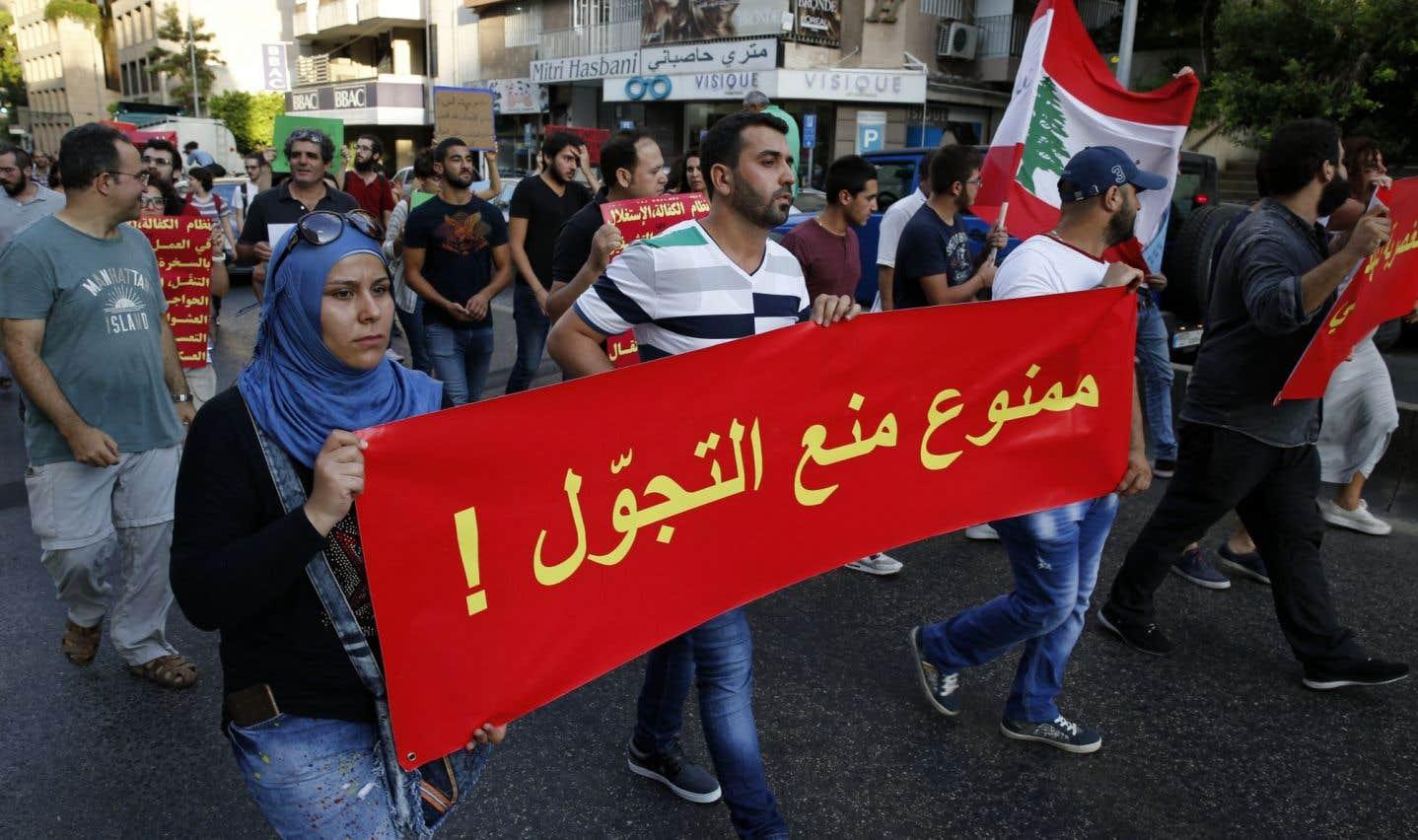 À Beyrouth, des manifestants soutenant les réfugiés tiennent une banderole sur laquelle il est écrit: «Il est interdit d'imposer un couvre-feu.»