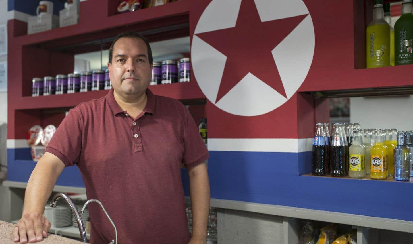 Alejandro Cao de Benos derrière le comptoir de l'établissement, où est peint un immense drapeau nord-coréen