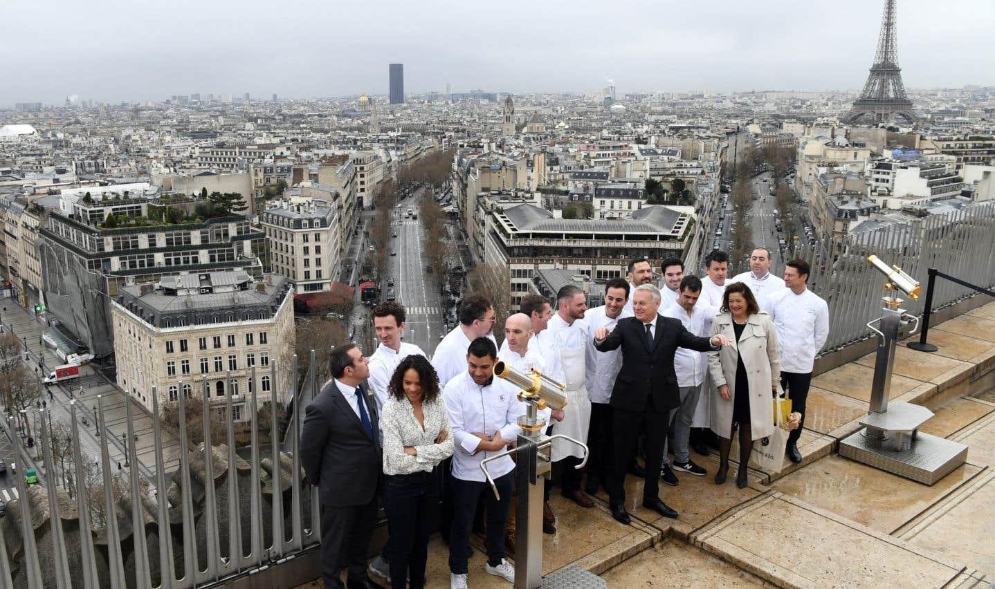 Jean-Marc Ayrault et Alain Ducasse posent en compagnie de jeunes apprentis cuisiniers au sommet de l'Arc de Triomphe, à Paris.