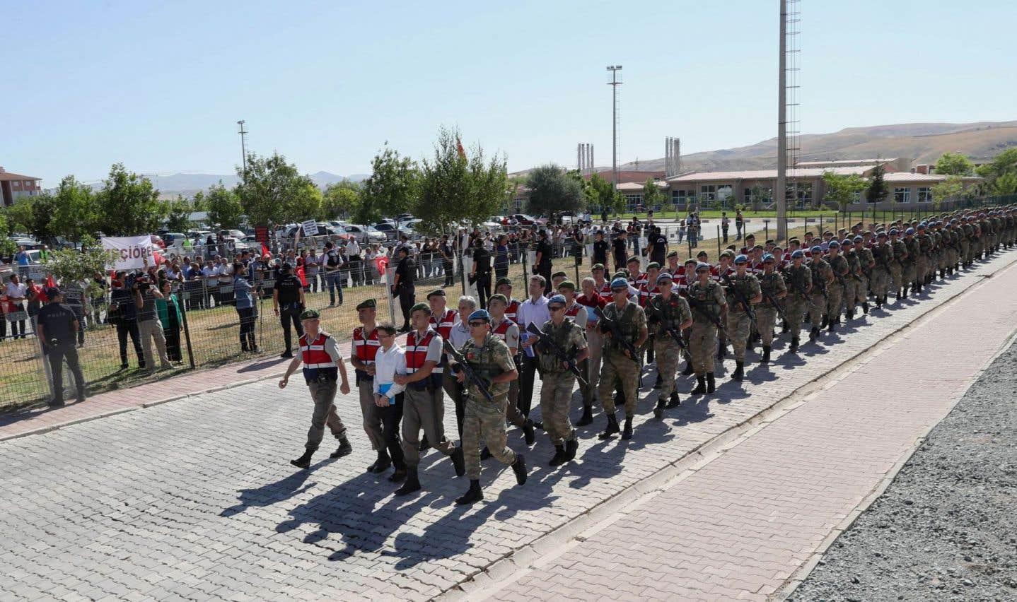 Mardi, 41 accusés ont été contraints de marcher depuis leur cellule jusqu'à une salle d'audience spécialement construite sur le site de la prison où ils sont détenus. Ils étaient menottés et escortés chacun par deux policiers paramilitaires.