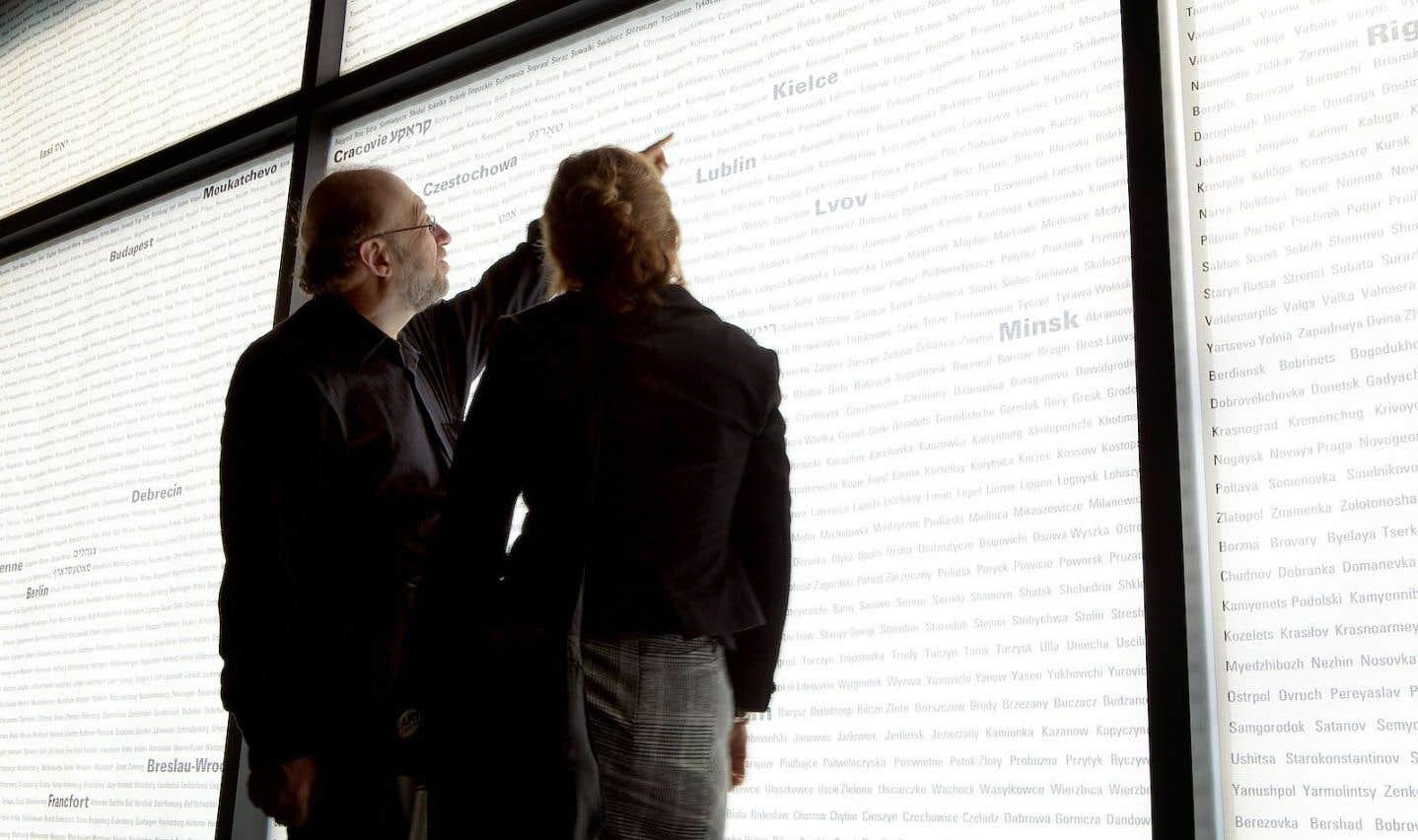 Des visiteurs dans la salle de commémoration où sont écrits les noms des milliers de villes, villages et shtetls en Europe et en Afrique du Nord qui ont été tyrannisés par les nazis et leurs collaborateurs.