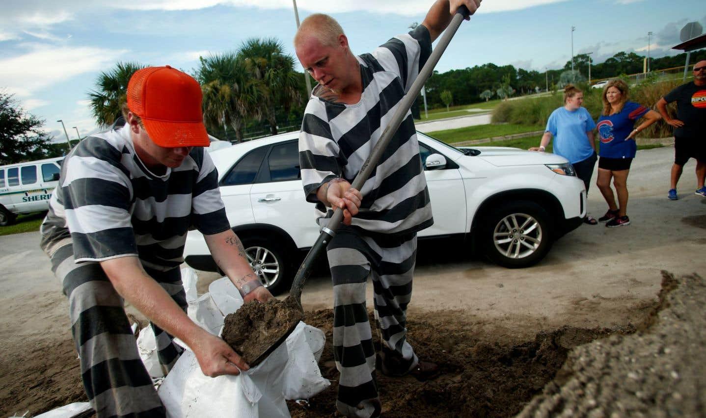 Des détenus de la prison du comté de Brevard chargent des sacs de sable alors que les gens de la région se préparent à l'arrivée de l'ouragan «Irma», à Meritt Island, en Floride.