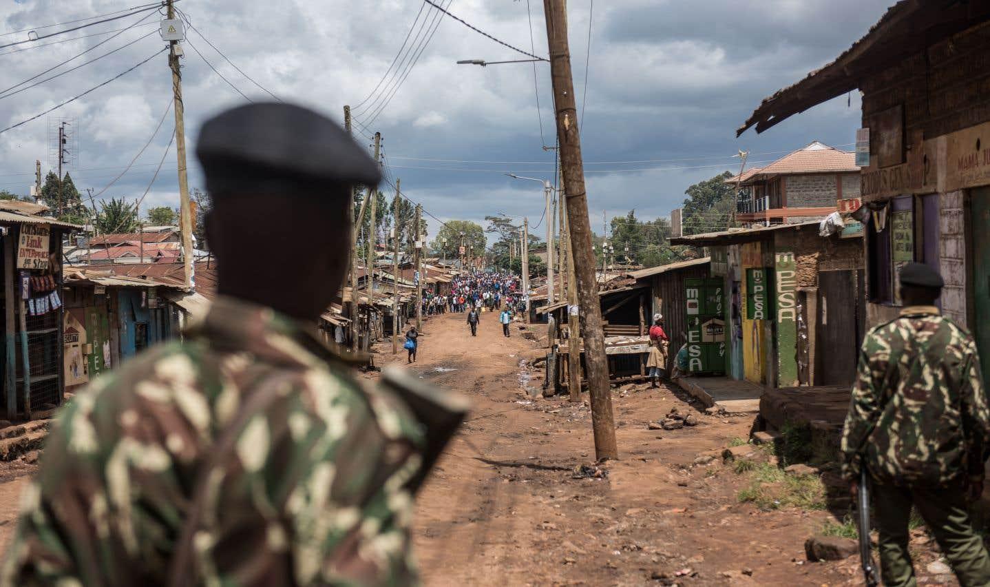 Des policiers montent la garde alors que des manifestants se rendent au bureau de vote de Gatina dans le district de Kawangware à Nairobi.