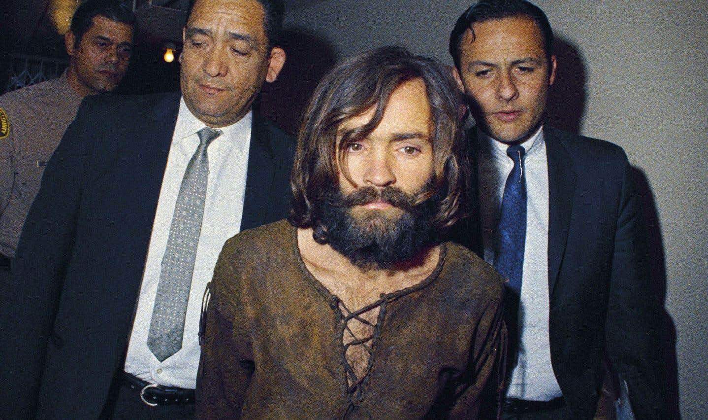 Charles Manson est escorté par des policiers à Los Angeles pour être accusé d'avoir orchestré les meurtres de l'actrice Sharon Tate et de six autres personnes.
