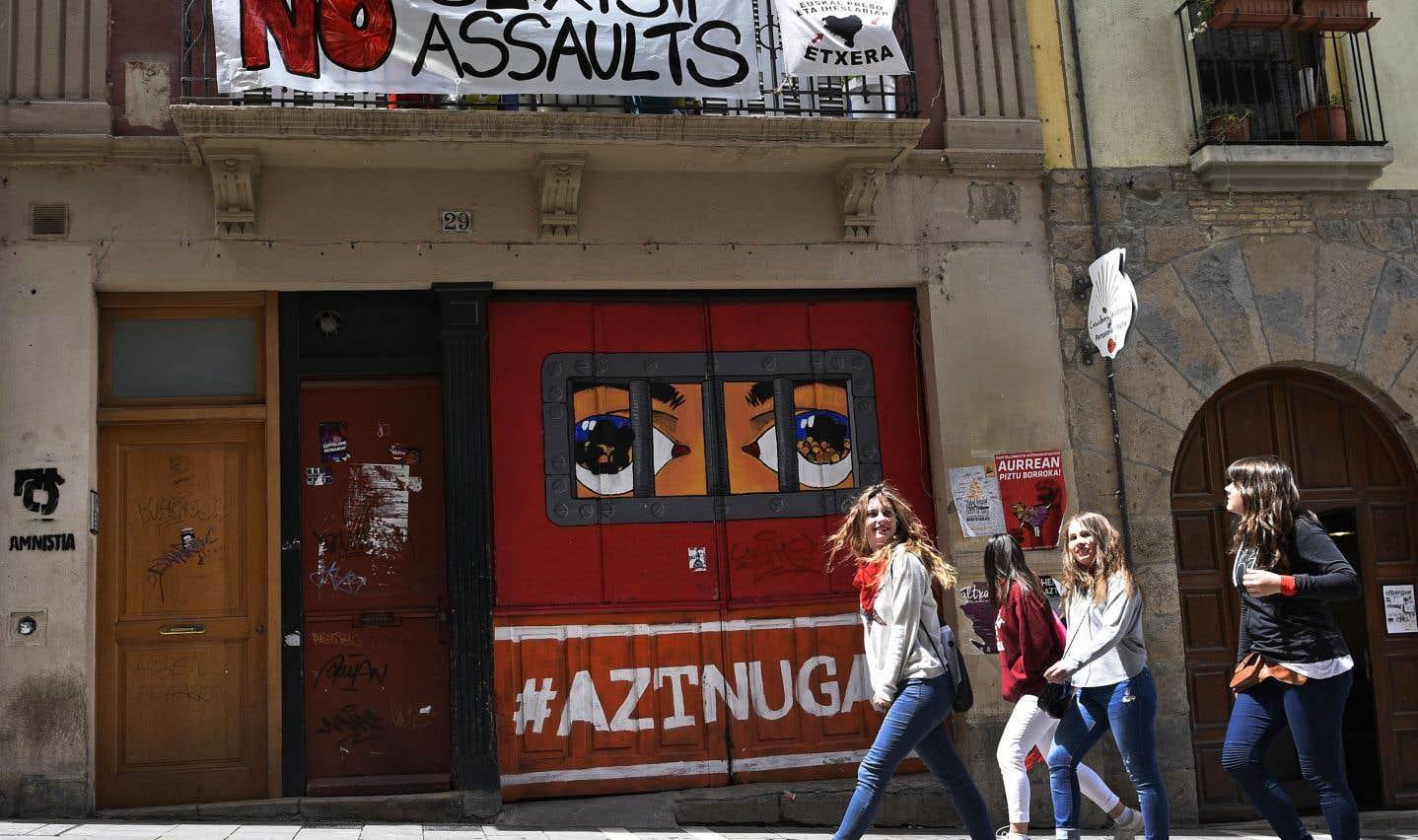 Des passantes marchaient sous une affiche dénonçant l'augmentation des agressions sexuelles pendant les festivités de la San Fermin, à Pampelune, en 2016.