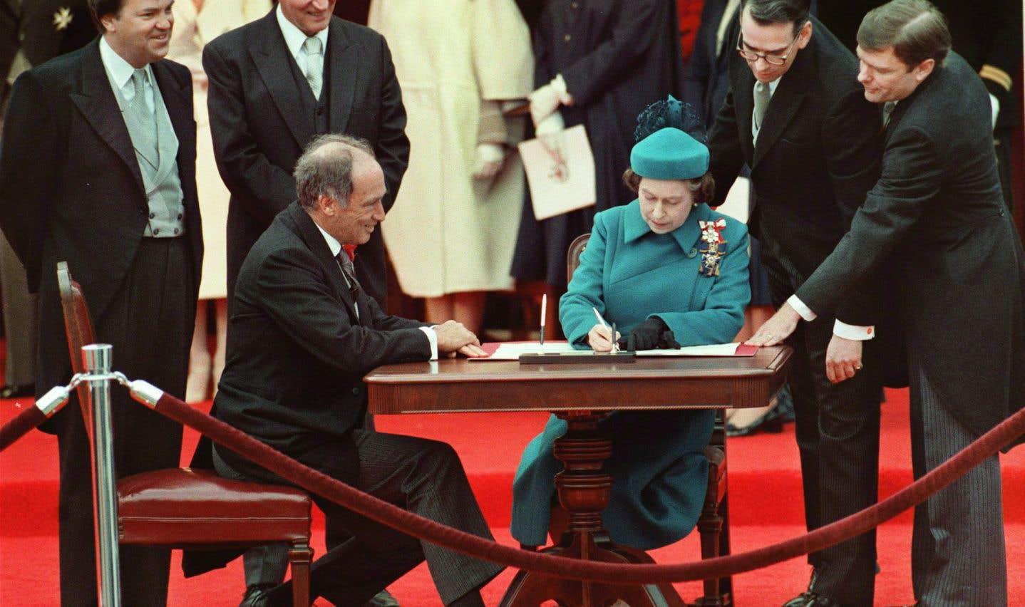 La reine Elizabeth II et le premier ministre Pierre Elliot Trudeau, au moment de signer la Loi de 1982, qui a permis le rapatriement de la Constitution canadienne en avril 1982.