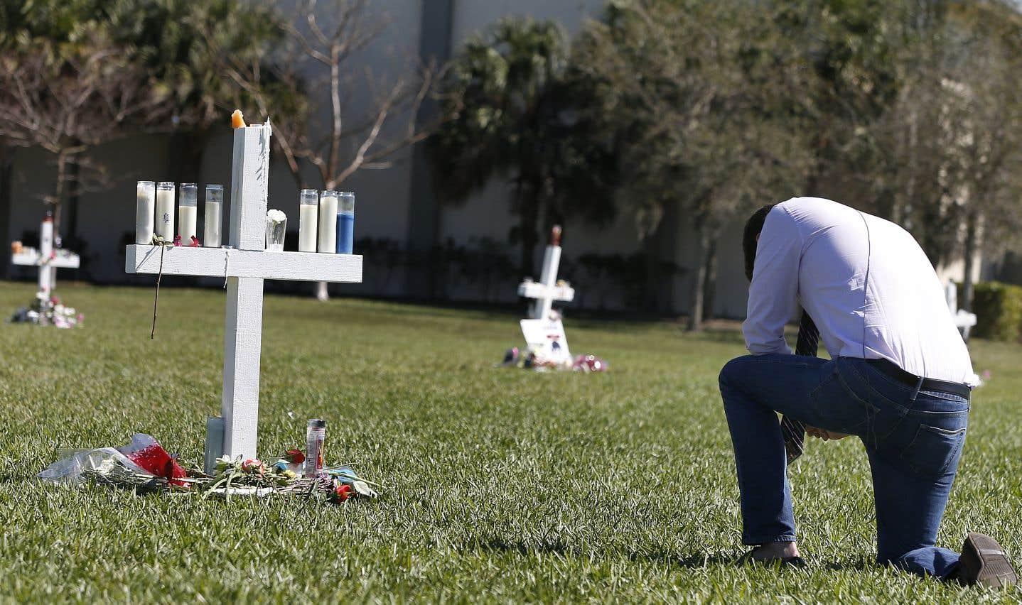 Un homme se recueille devant un mémorial à la mémoire des victimes de la fusillade de l'école Marjory Stoneman Douglas.