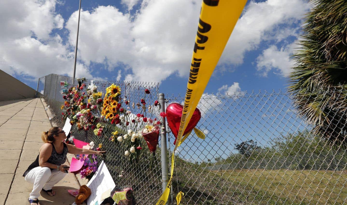 Une dame place des fleurs sous un viaduc, près du lycée Marjory Stoneman Douglas, où des étudiants ont cherché refuge après la tuerie de mercredi.