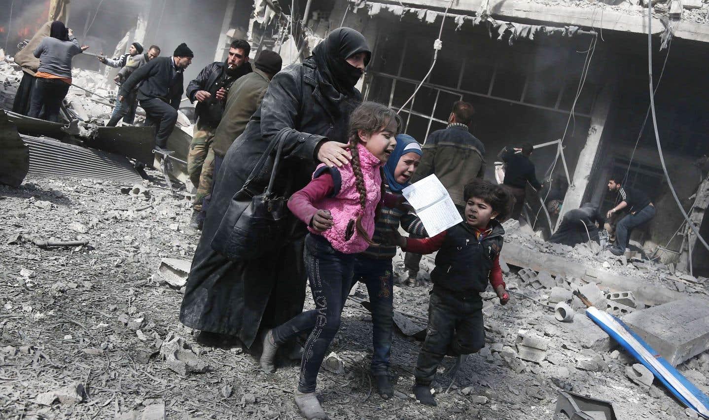 Une femme et des enfants syriens courent se mettre à l'abri des bombardements de l'armée syrienne sur la ville rebelle de Hamouria, en Ghouta orientale.