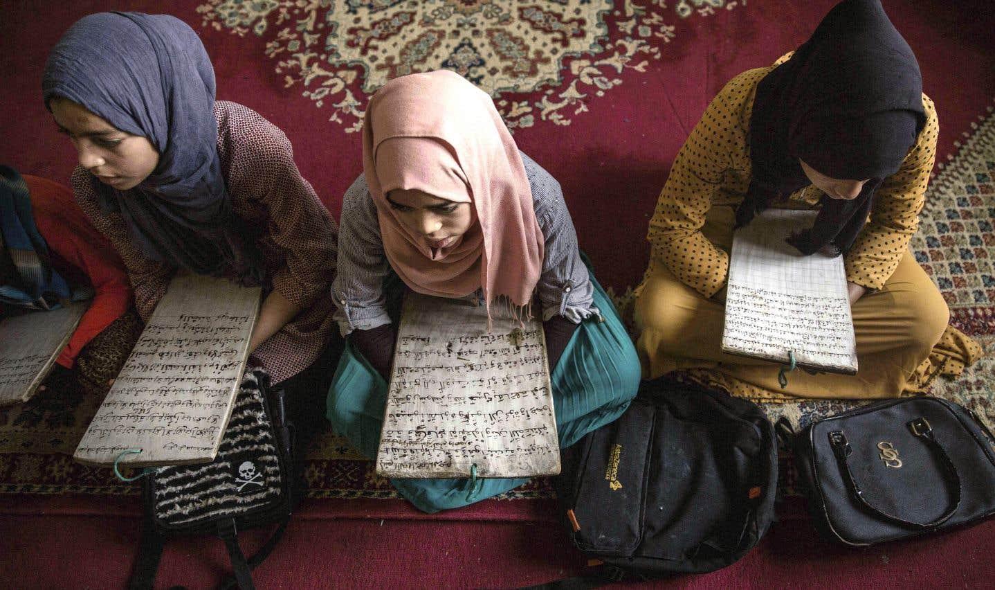 De jeunes filles apprennent à lire et à écrire le Coran sur le banc d'une école du sud du Maroc, lors du premier jour du ramadan.
