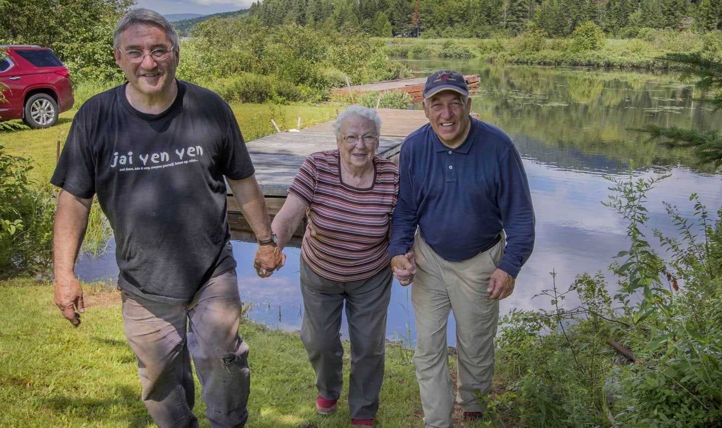Jeannine Regimbal marche sur son terrain en compagnie d'André Gaudet et de Jacques Deguire. Après la découverte de l'avion, les familles des défunts passaient devant la maison de cette dame de 89 ans pour traverser le lac Archambault, puis gravir la montagne Noire.