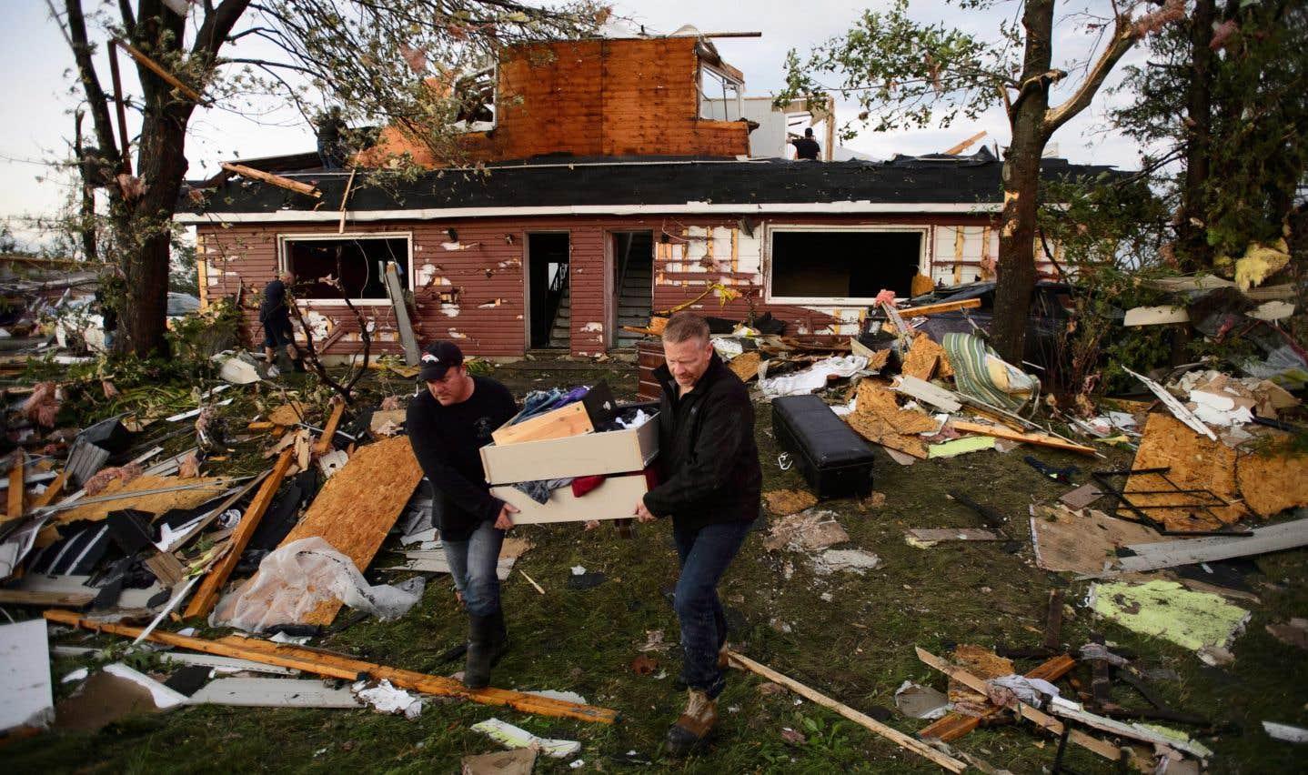 Des gens ramassent des effets personnels dans leur maison endommagée après le passage d'une tornade à Dunrobin, en Ontario, à l'ouest d'Ottawa, le vendredi 21 septembre 2018.