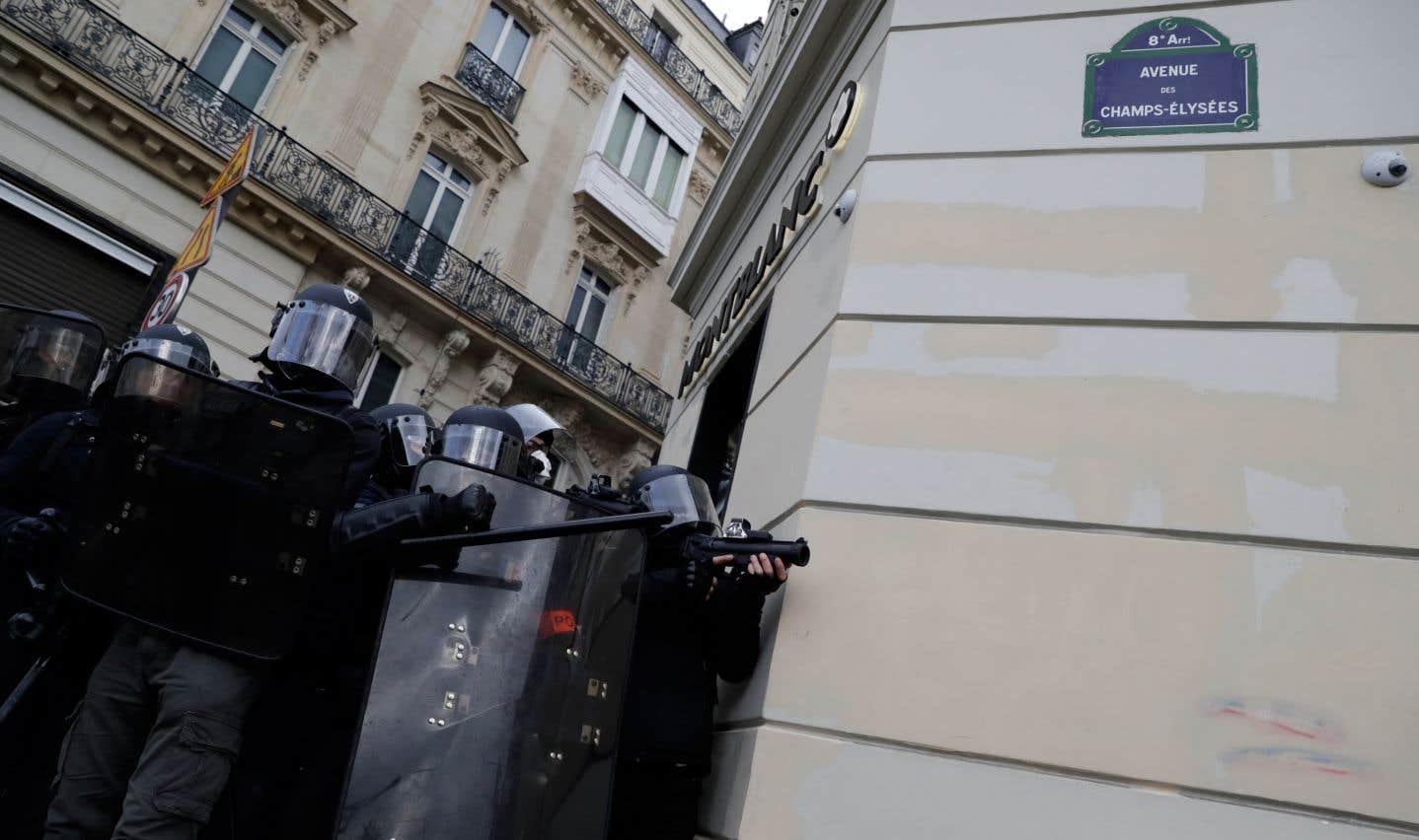 Des policiers anti-émeute sur l'avenue des Champs-Élysées, à Paris.