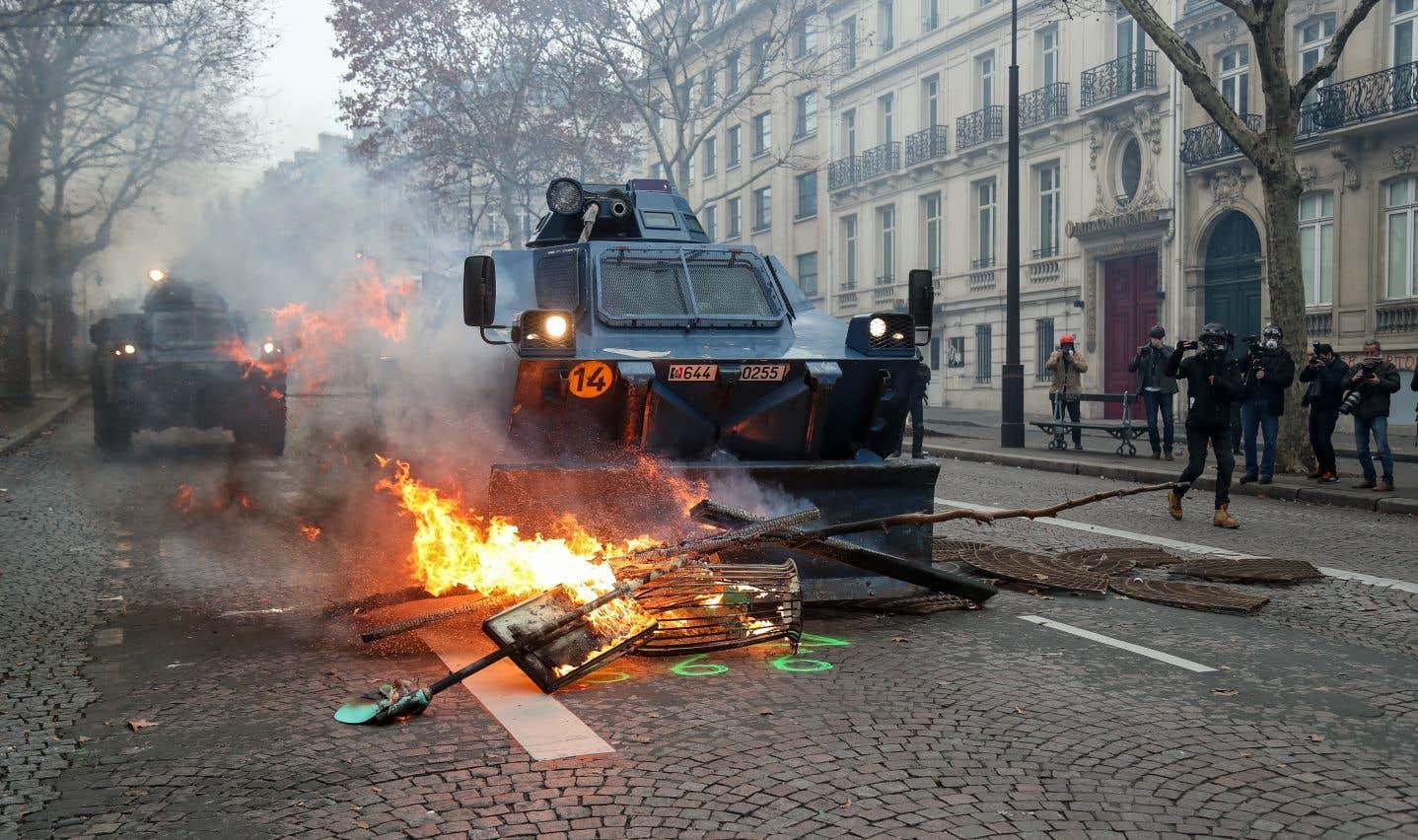 Un véhicule blindé de la Gendarmerie déloge une barricade enflammée près de l'avenue des Champs-Élysées, à Paris.