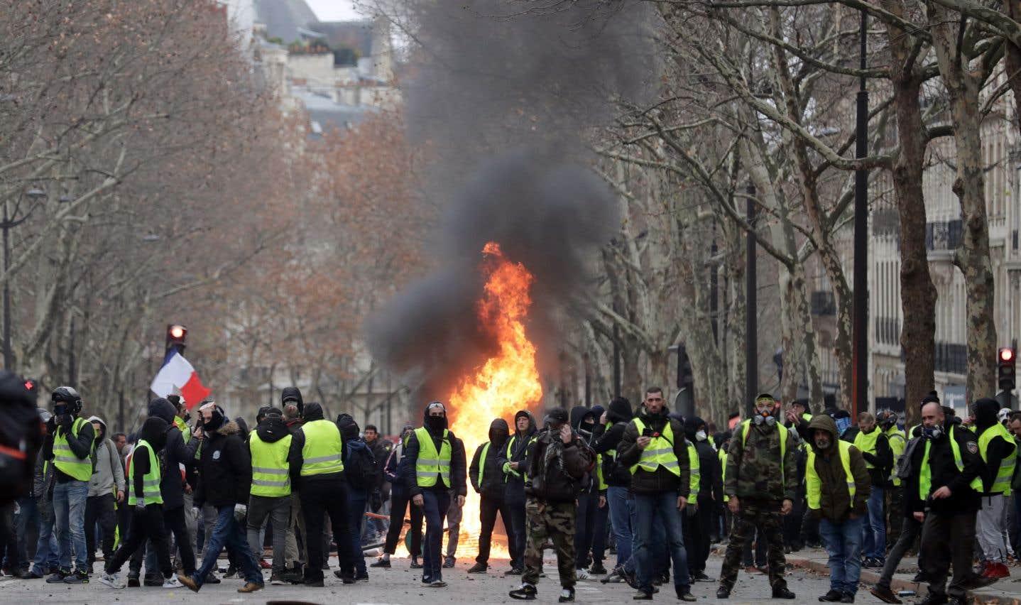 Des manifestants sont rassemblés près d'un feu, près de l'avenue des Champs-Élysées, à Paris.
