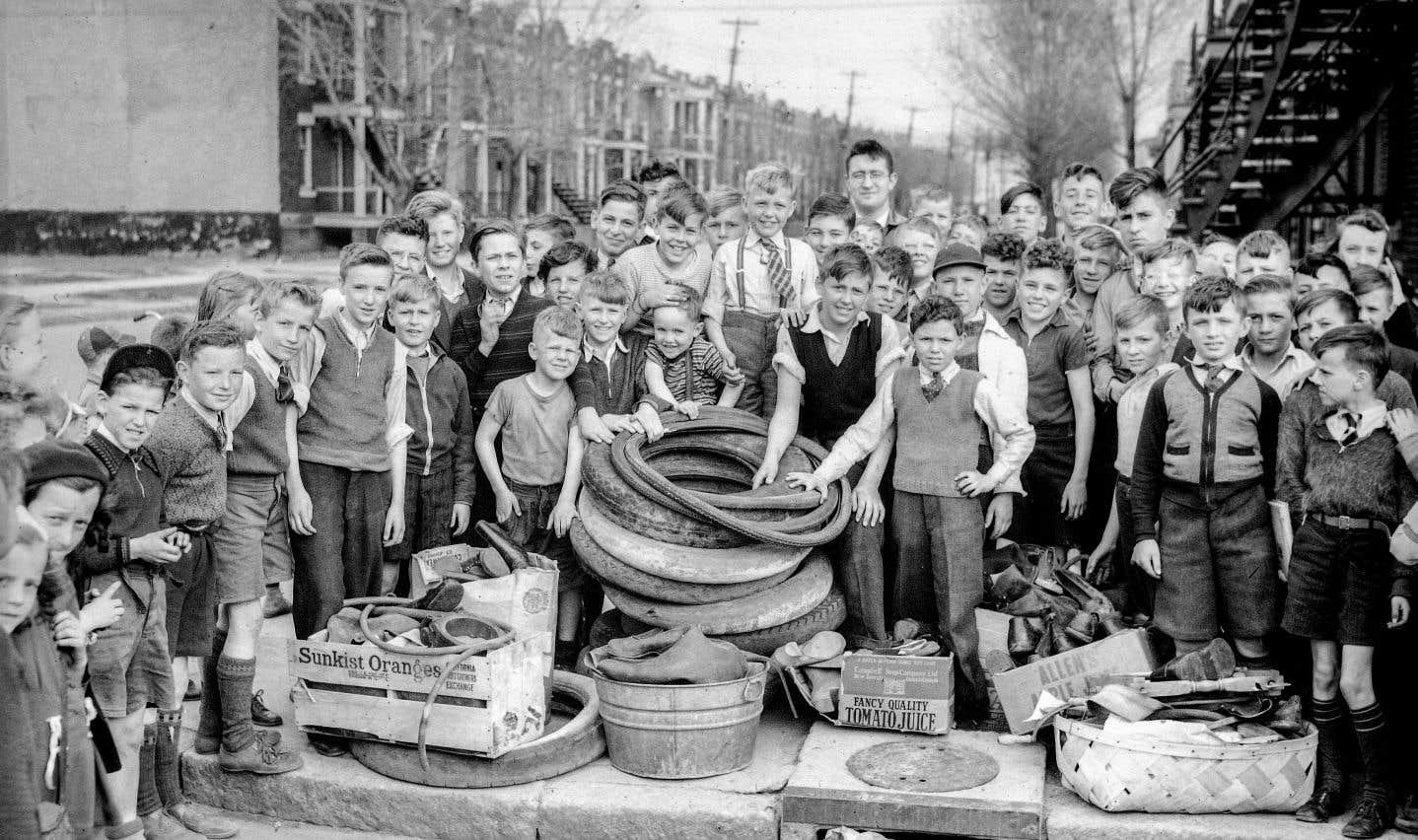 Des enfants du quartier Rosemont posent pour Conrad Poirier avec des dizaines de pneus en caoutchouc qu'ils ont récupérés. 29avril 1942.