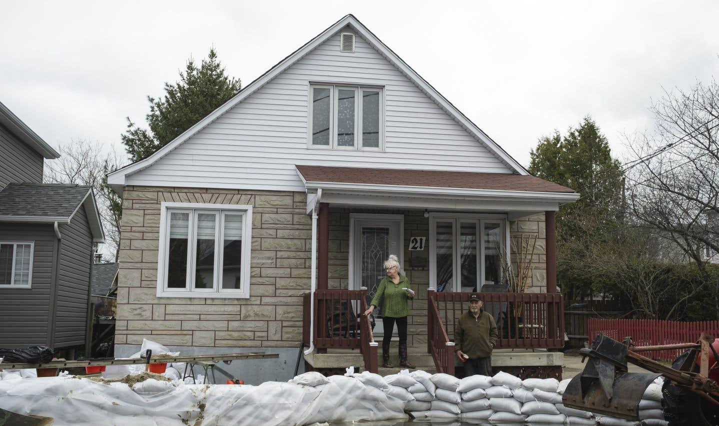 Devant la résidence de Louise Klimko, 75 ans, la rue Harriett à Lachute n'est plus qu'une rivière. Mais sa maison est encore bien au sec, protégée par une digue érigée par son voisin Michaël Décoste.