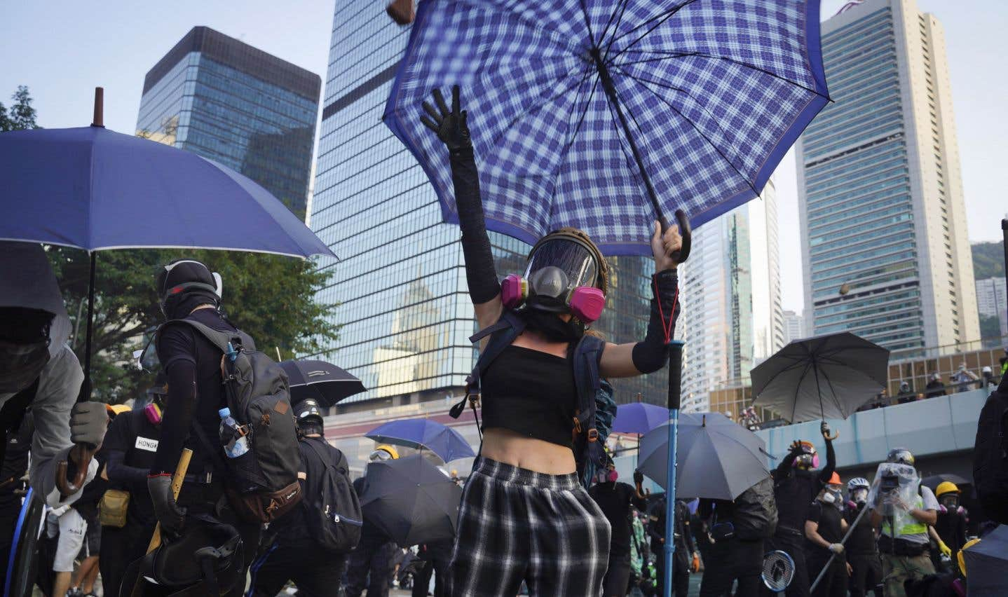 Des protestataires lancent des pierres durant une manifestation contre le gouvernement. Le rassemblement a généré des affrontements entre des policiers et des groupuscules radicaux. Malgré l'interdiction de manifester, des centaines de personnes se sont présentées devant le consulat britannique pour réclamer davantage d'actions de Londres pour son ancienne colonie.