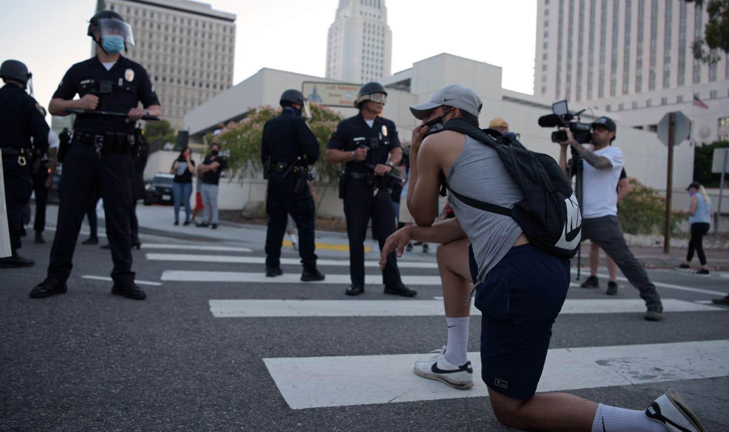Un manifestant s'agenouille devant une rangée de policiers alors que des manifestants se rassemblent au centre-ville de Los Angeles pour manifester contre la mort de George Floyd.