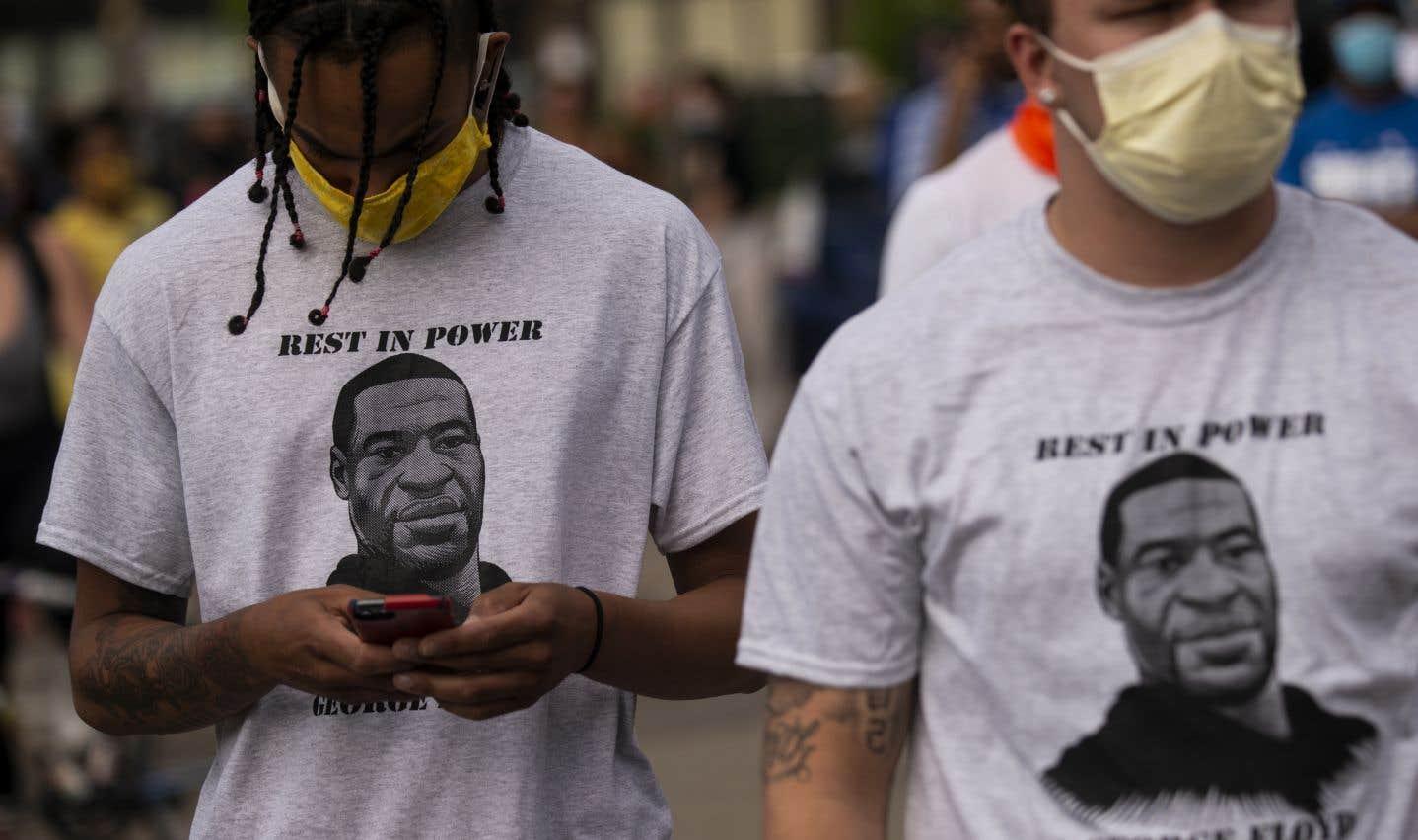 Deux hommes portent des chandails sur lesquels il est écrit «Repose en puissance George Floyd», à l'extérieur de poste de police no. 3, à Minneapolis.