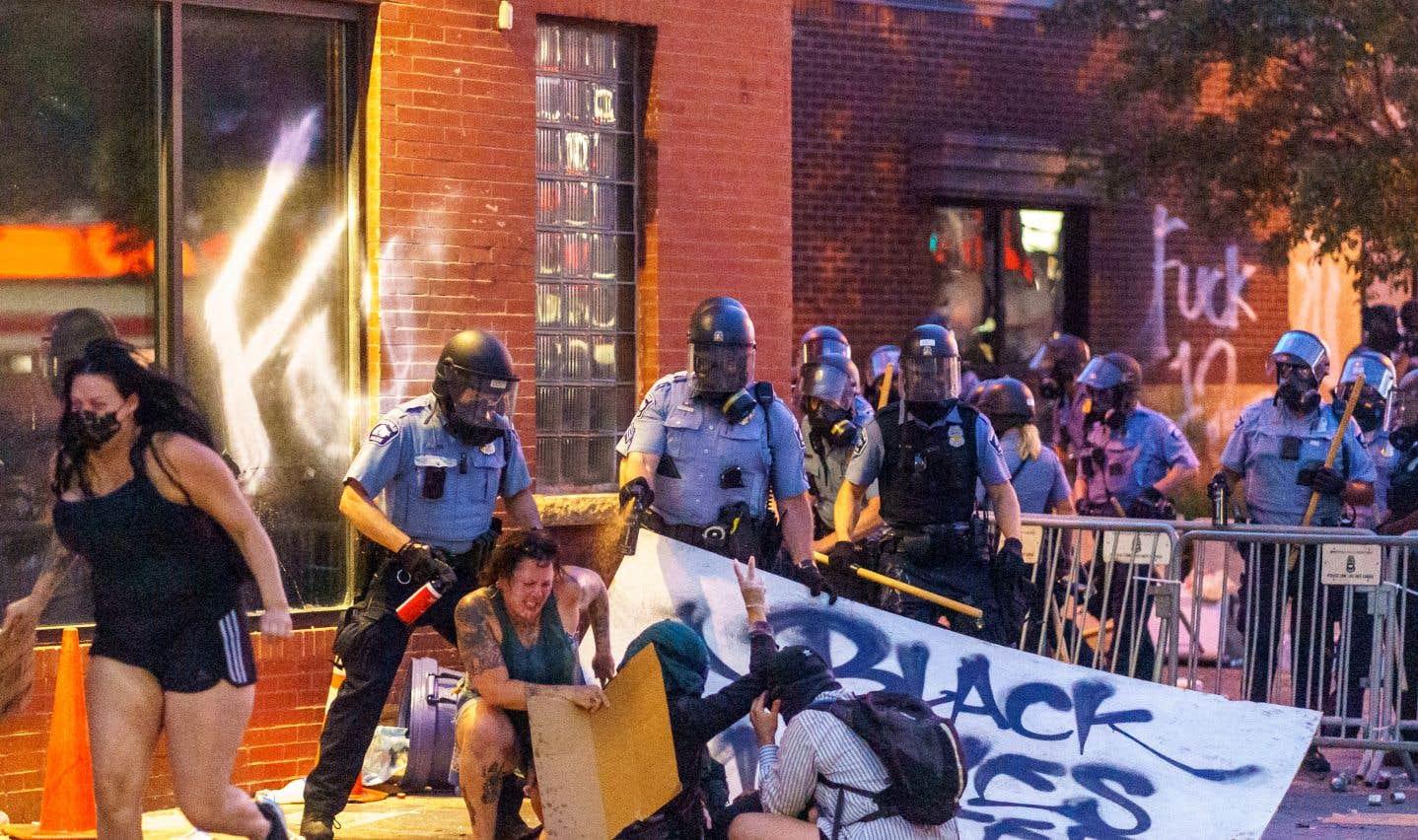 Des policiers arrosent des manifestants avec du poivre de cayenne lors d'une manifestation contre le meurtre de George Floyd à l'extérieur poste de police no. 3 à Minneapolis.
