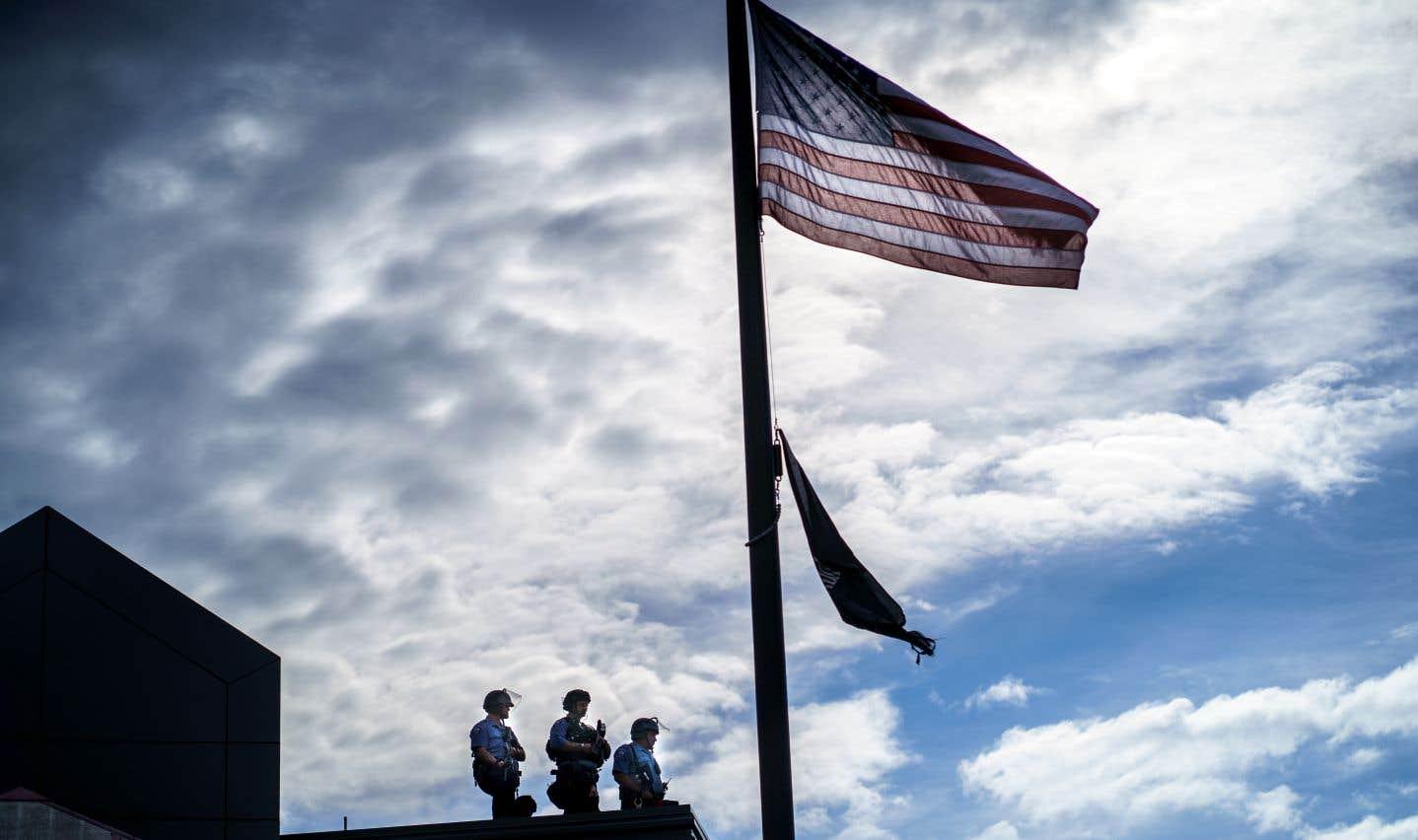 Trois policiers se tiennent sur le toit du poste de police no. 3, l'un tenant une arme à projectile, alors que des manifestants affrontent la police à l'extérieur, à Minneapolis.